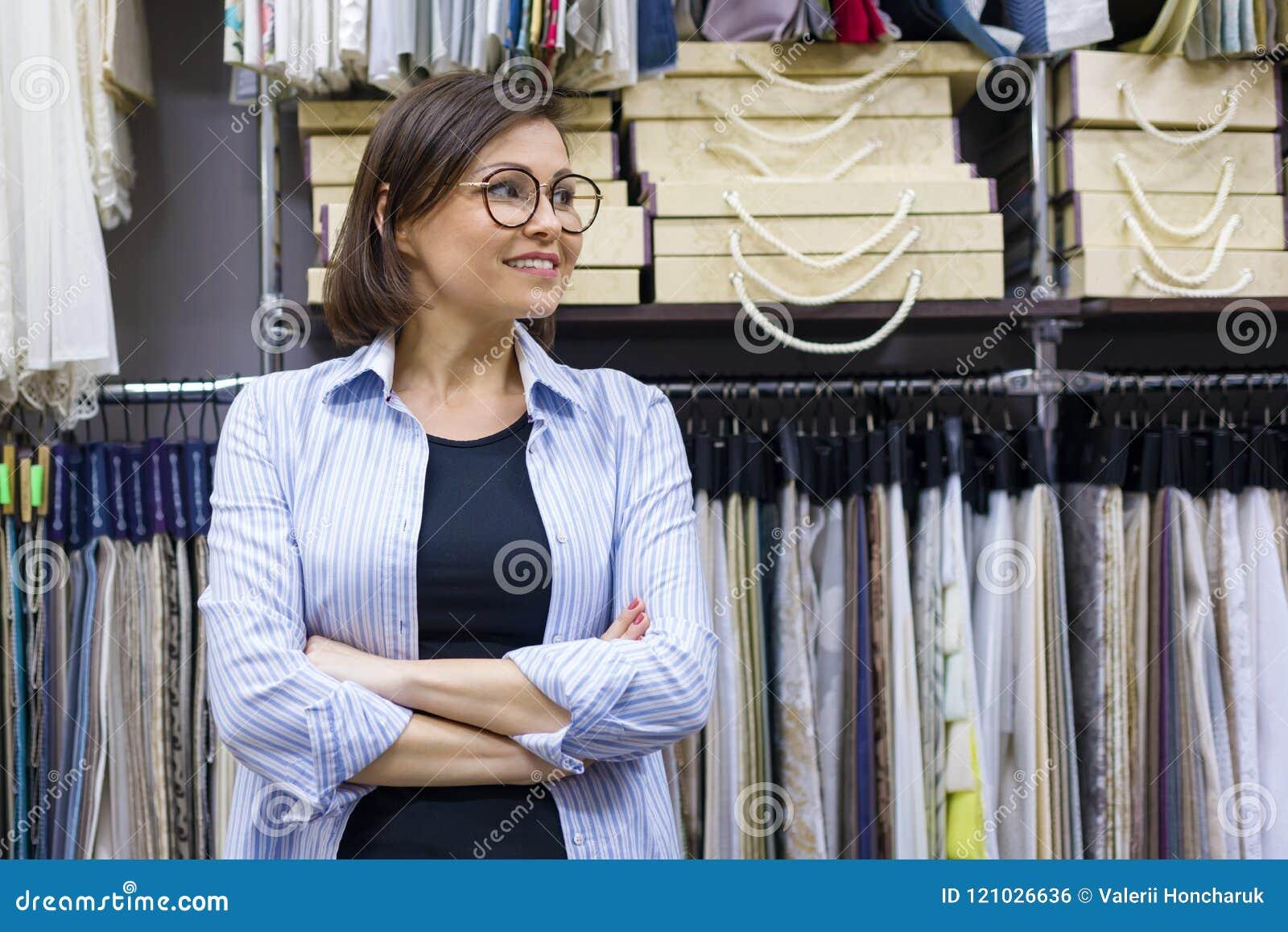 Ritratto del proprietario maturo felice della donna con le armi attraversate nel deposito interno dei tessuti, campioni del tessu