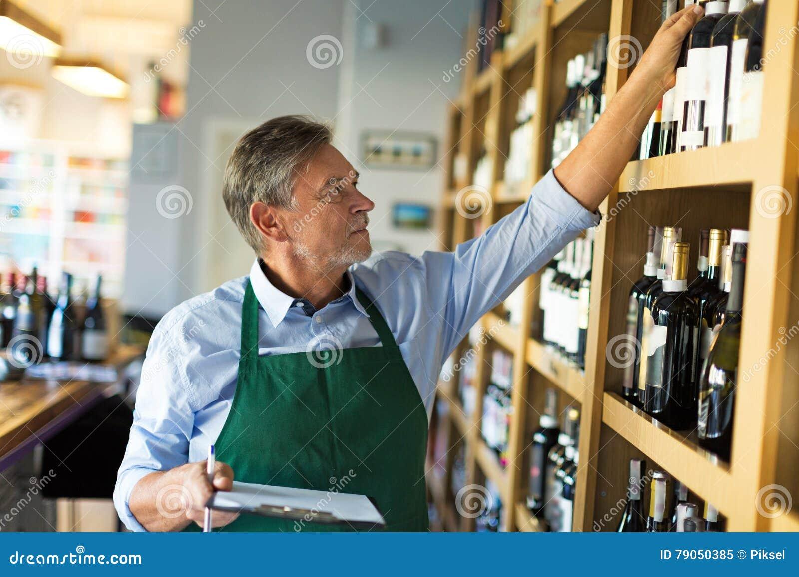 Ritratto del sommelier che prende inventario nel deposito di vino
