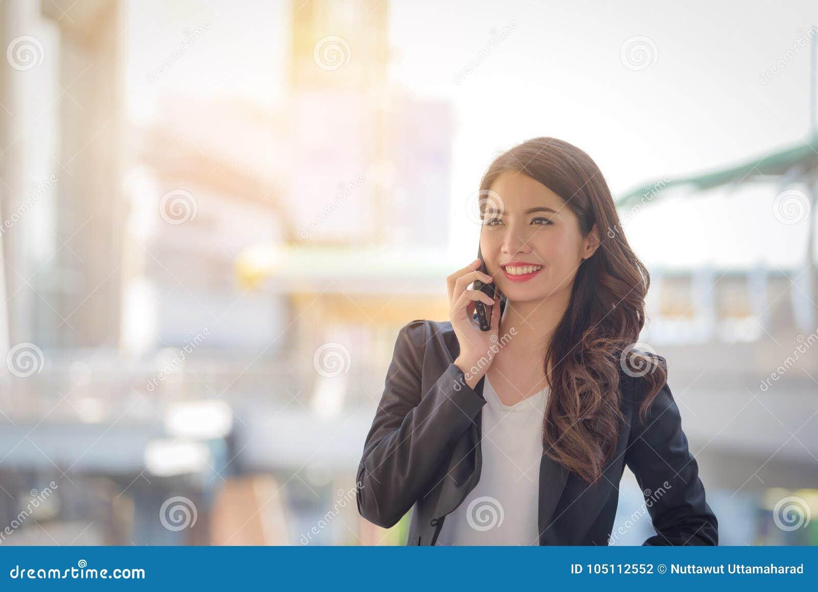 Ritratto del sorriso felice della donna di affari che parla sullo spirito dello smartphone