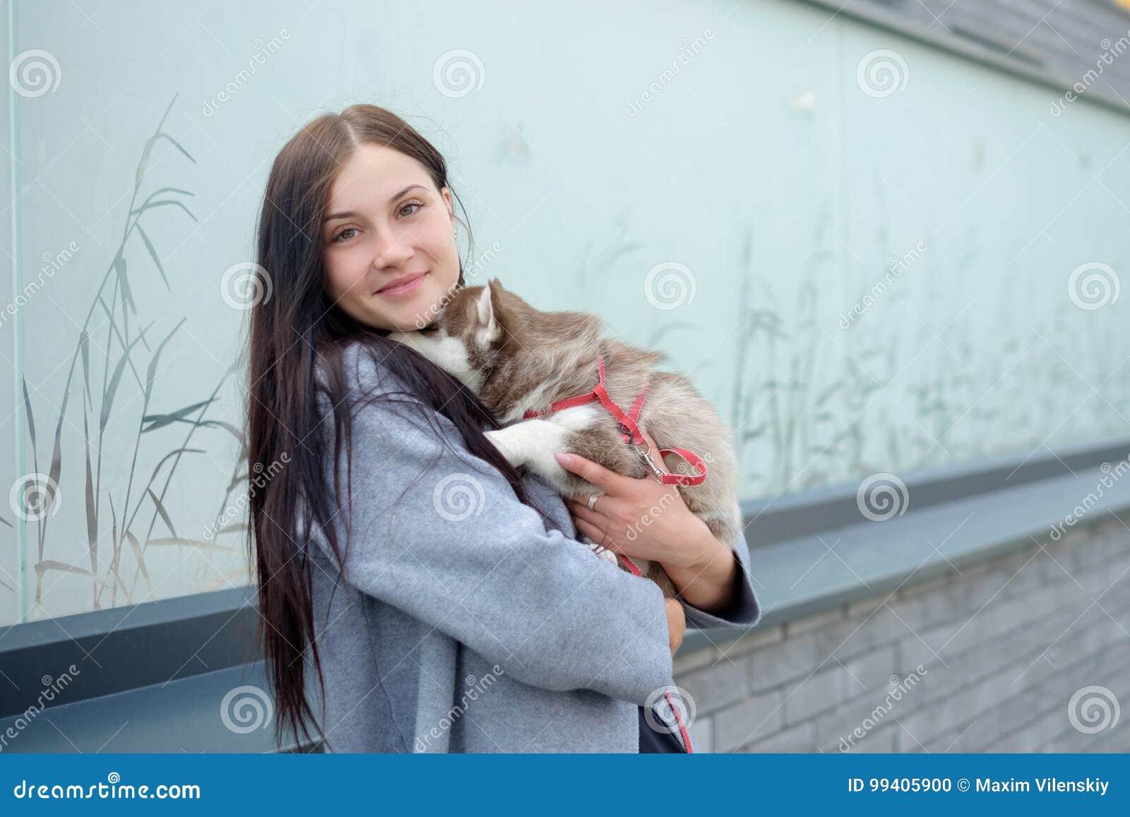 Ritratto dell giovani donne con i cuccioli di un husky