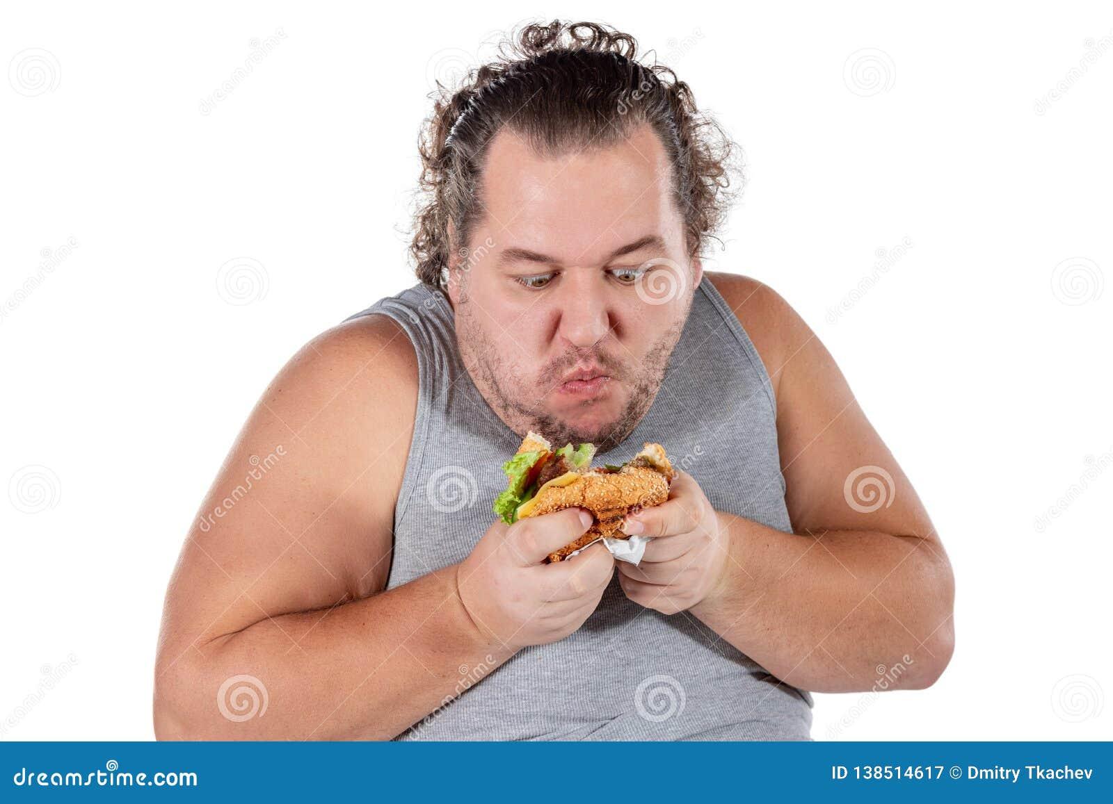 Ritratto dell hamburger mangiatore di uomini grasso divertente degli alimenti a rapida preparazione isolato su fondo bianco