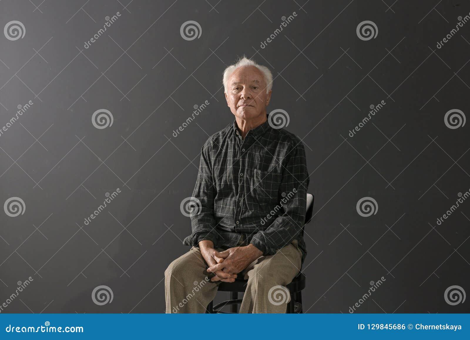 Ritratto dell uomo anziano povero che si siede sulla sedia