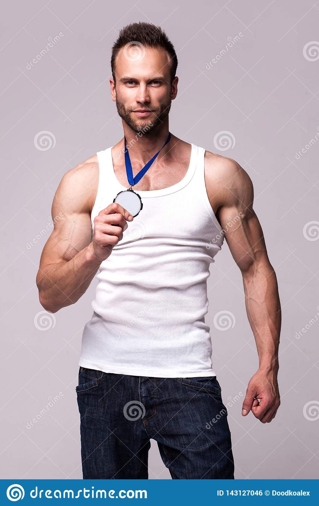 Ritratto dell uomo atletico in maglietta bianca con la medaglia dei campioni