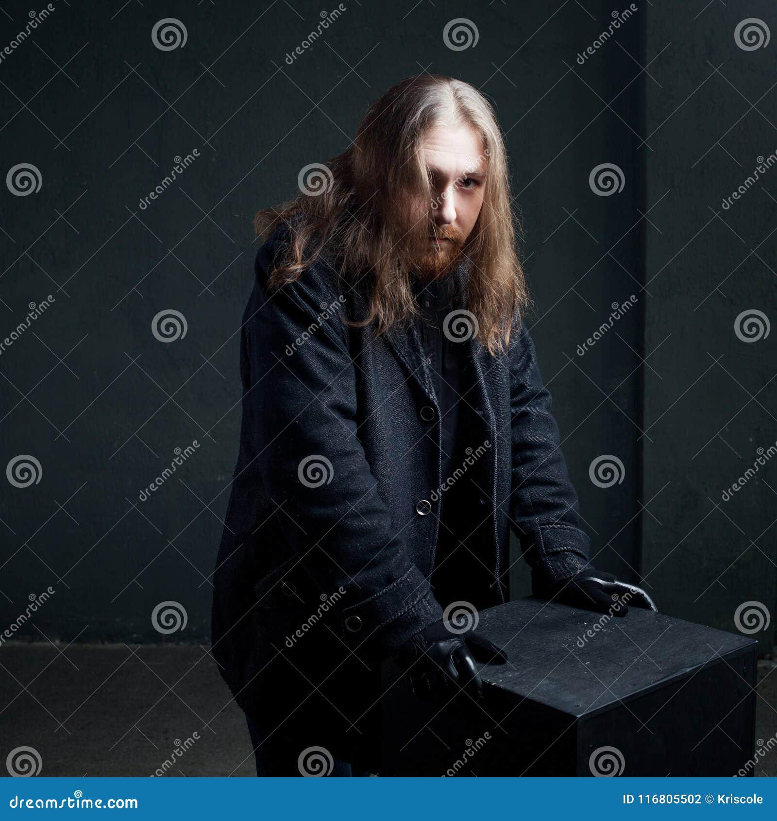 Ritratto dell uomo con capelli lunghi e della barba in vestiti neri su fondo scuro
