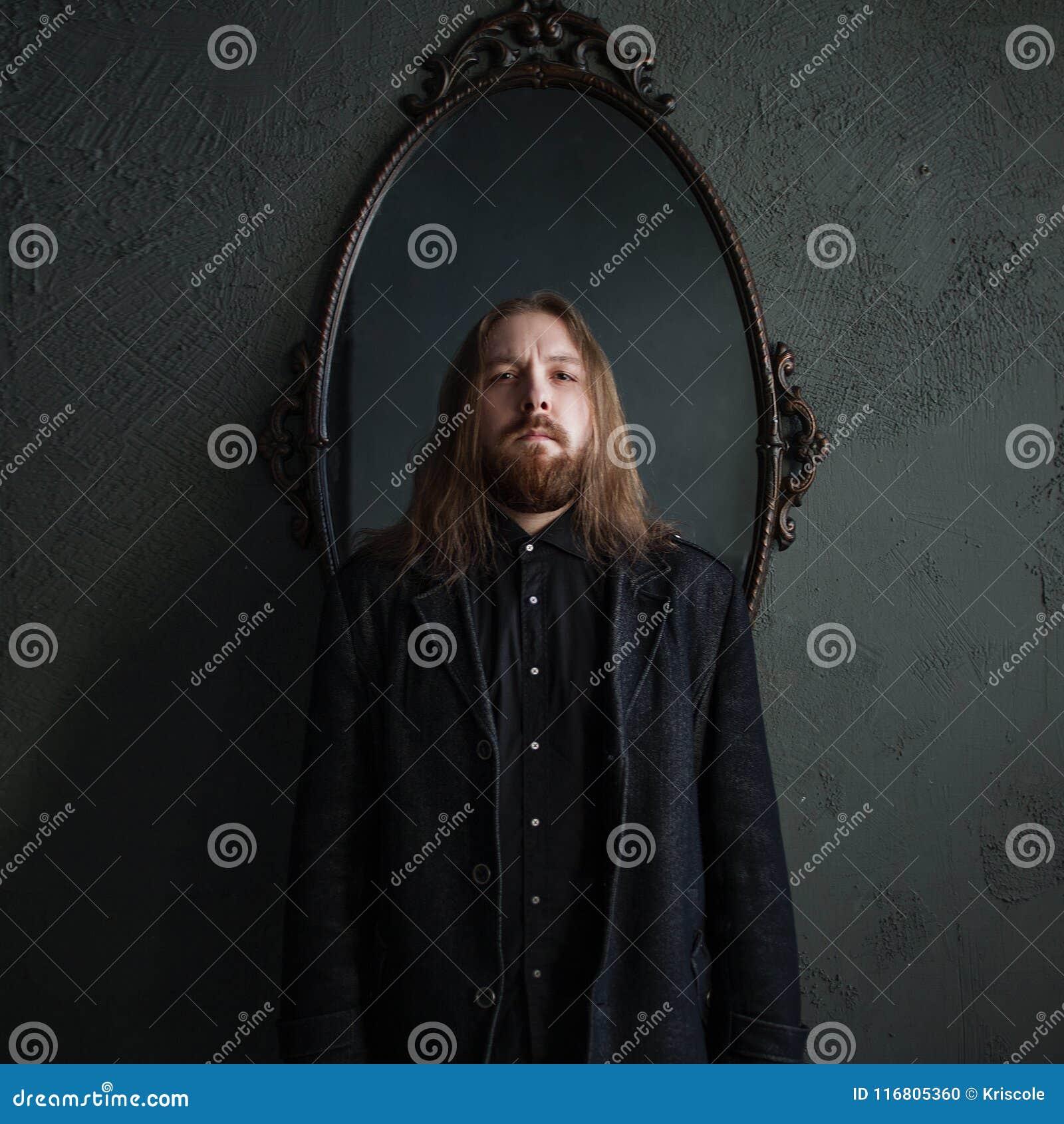Ritratto dell uomo con capelli lunghi e della barba in vestiti neri sui precedenti degli specchi