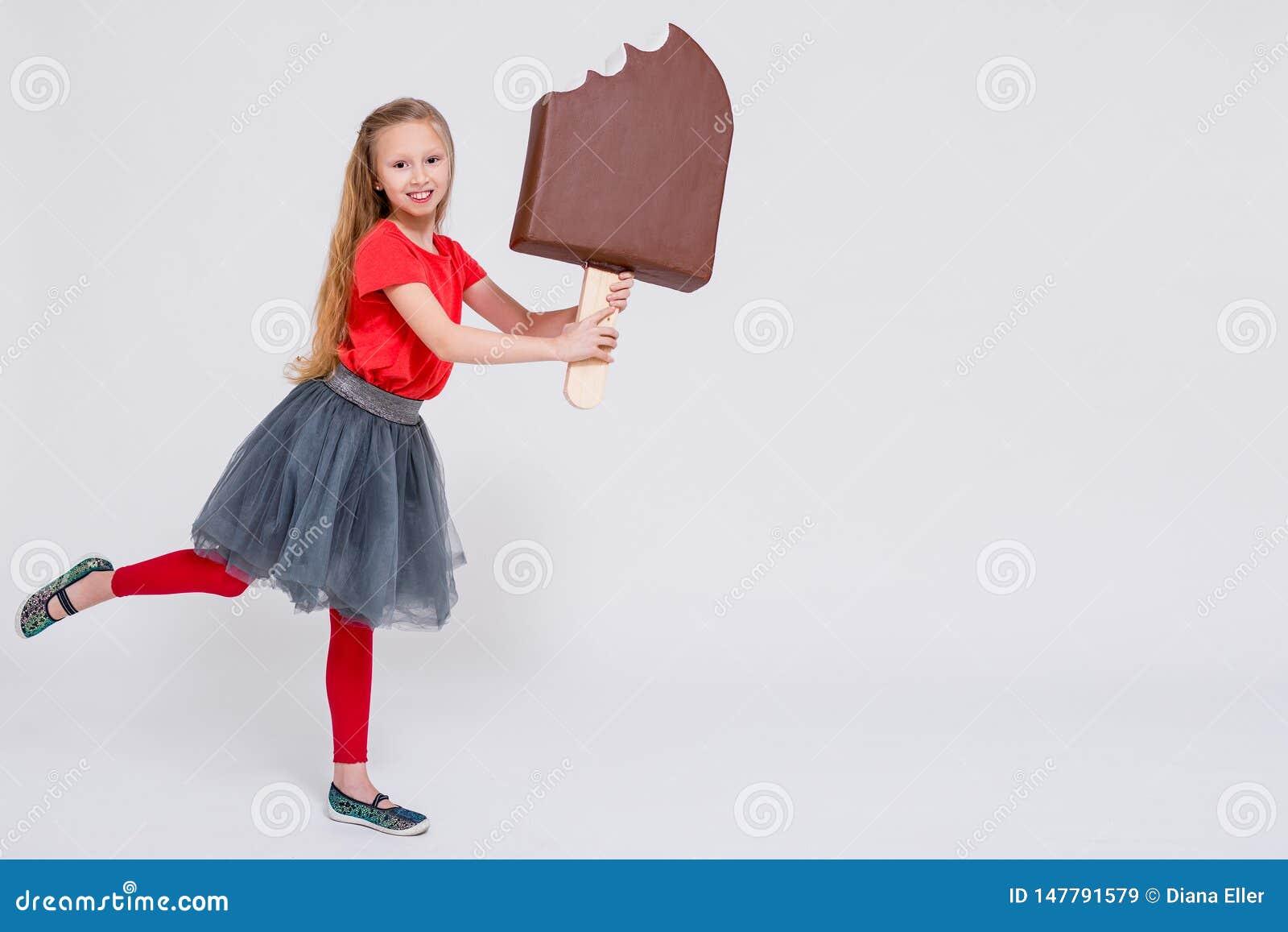 Ritratto della bambina sveglia che tiene il gelato e lo spazio enormi della copia sopra bianco