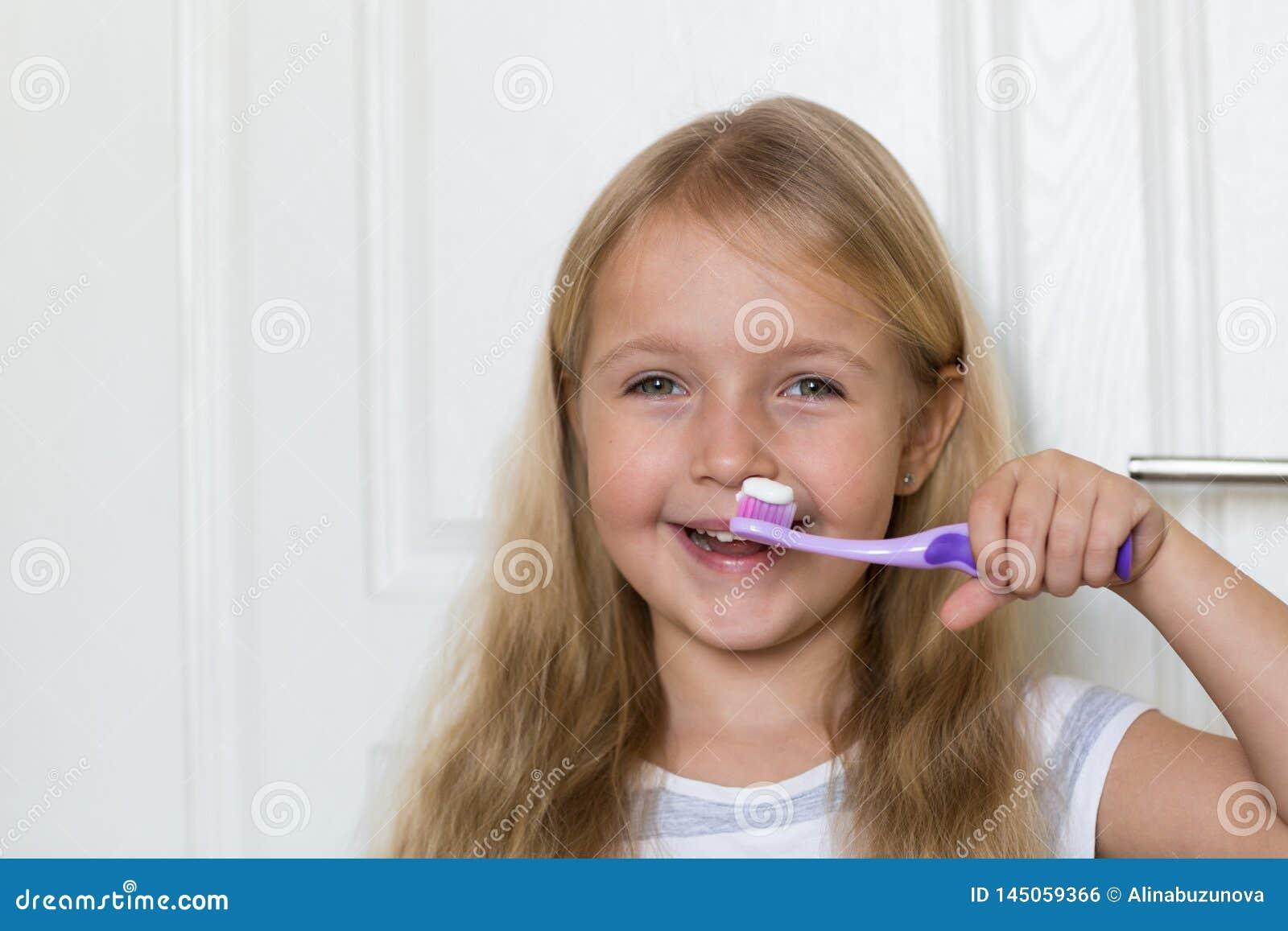 Ritratto della bambina sveglia con capelli biondi che dente di pulizia con la spazzola e dentifricio in pasta in bagno