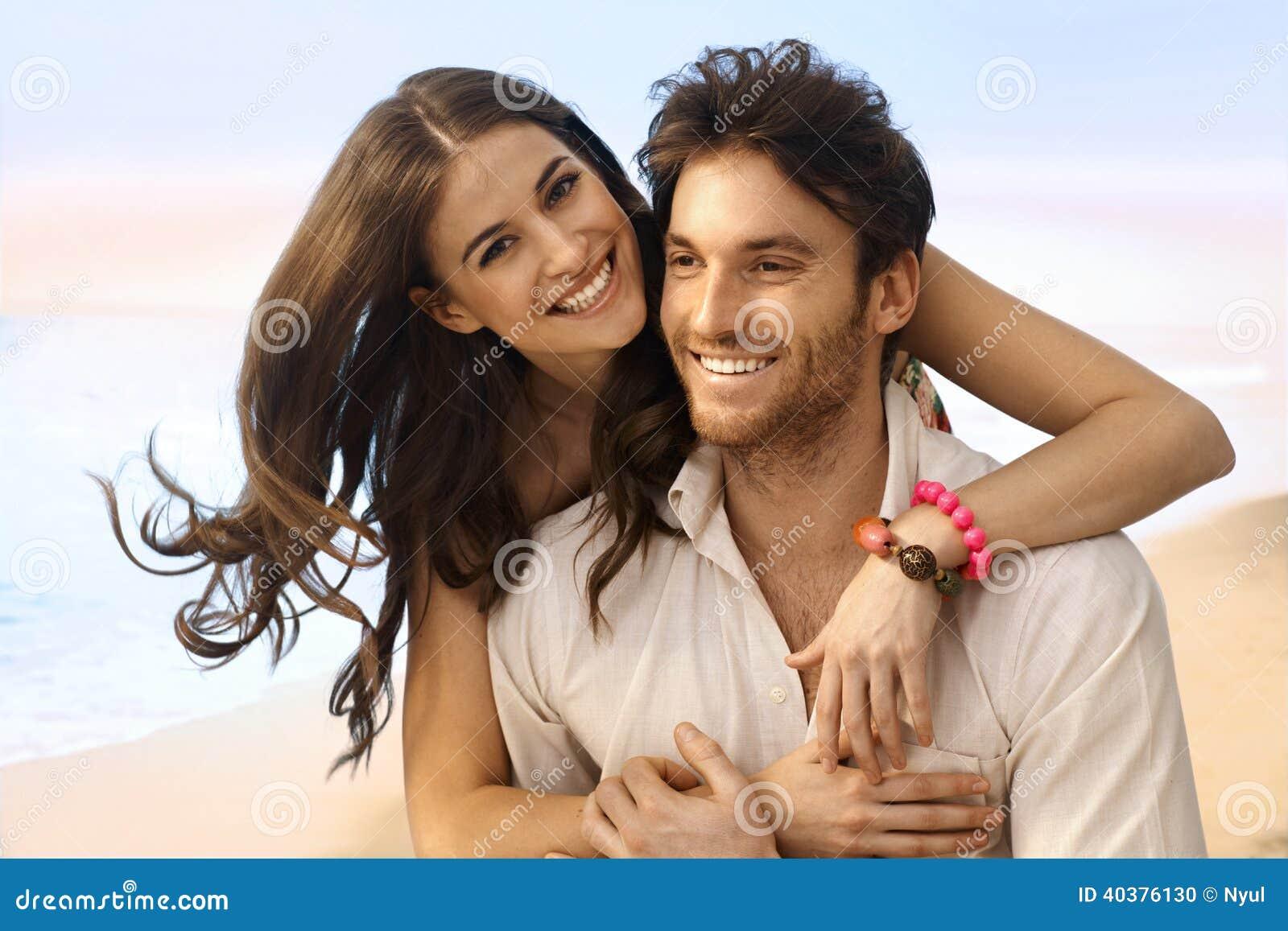 Ritratto della coppia sposata felice alla spiaggia