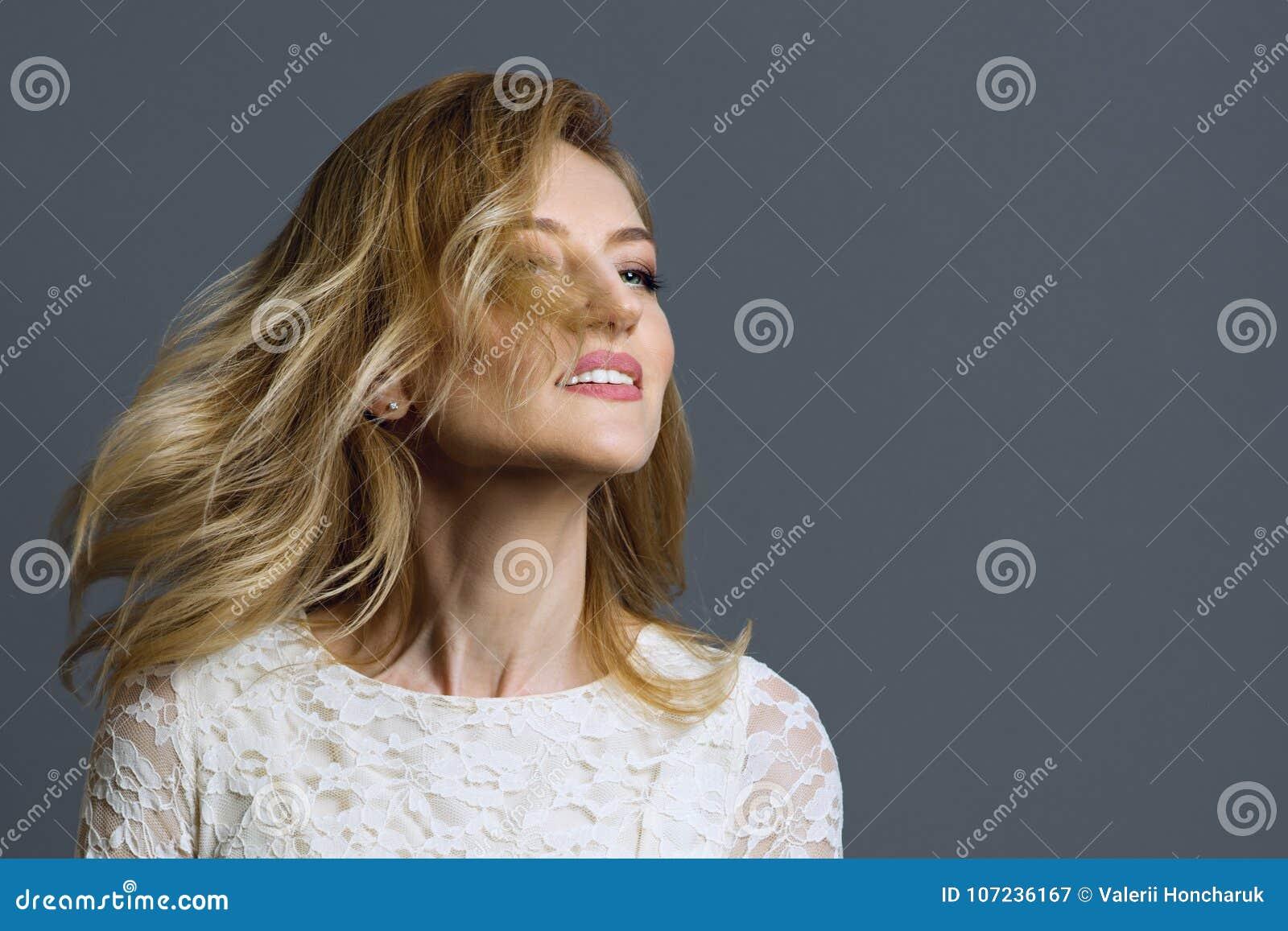 Ritratto della donna bionda adulta felice che fila il suo fondo capo e grigio