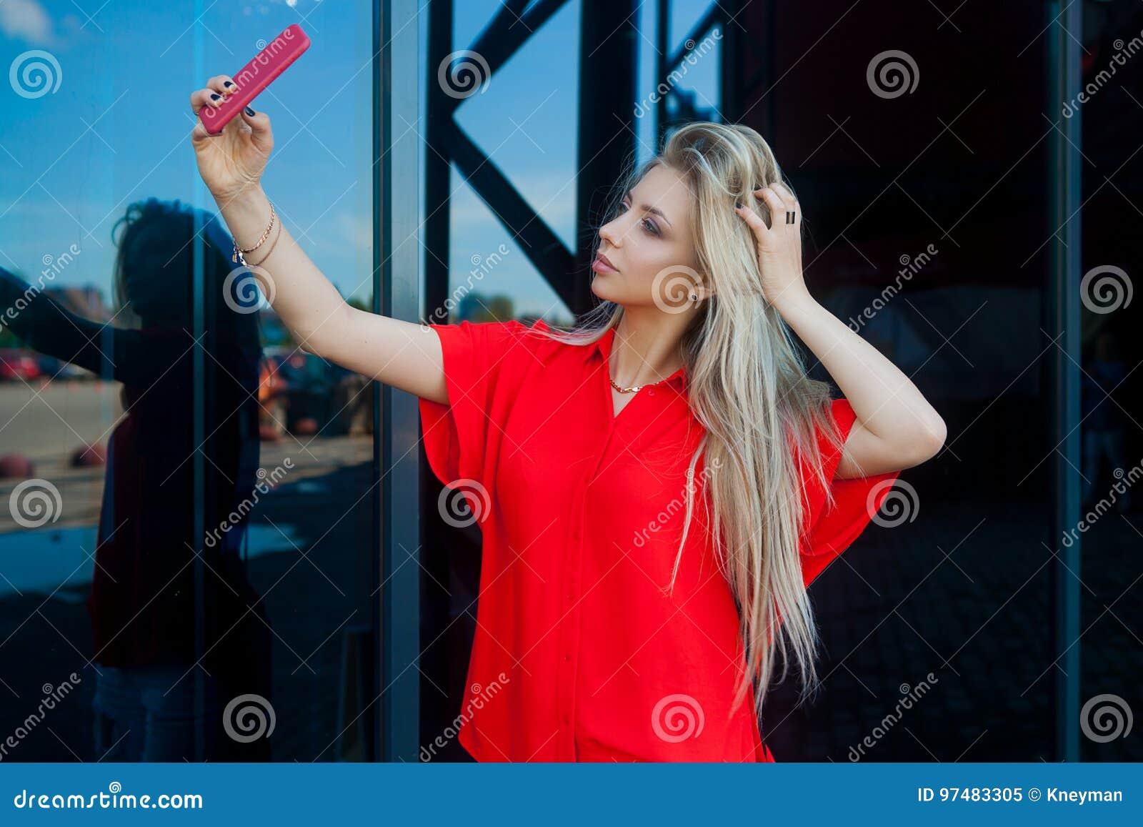 Ritratto della donna bionda sorridente di bellezza in camicia rossa con lo smartphone vicino all ufficio Fabbricazione del selfie