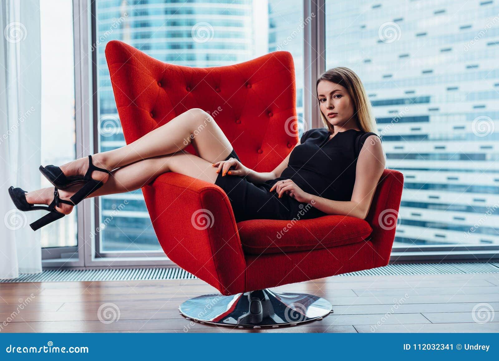 Ritratto della donna di affari sexy che si rilassa in poltrona alla moda all ufficio