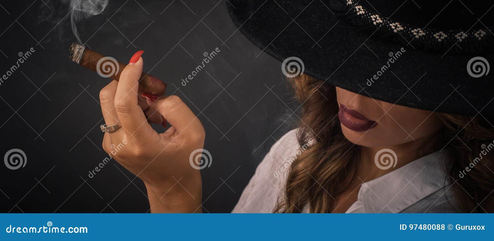 Ritratto della donna elegante sexy di signora con il sigaro di fumo del cappello