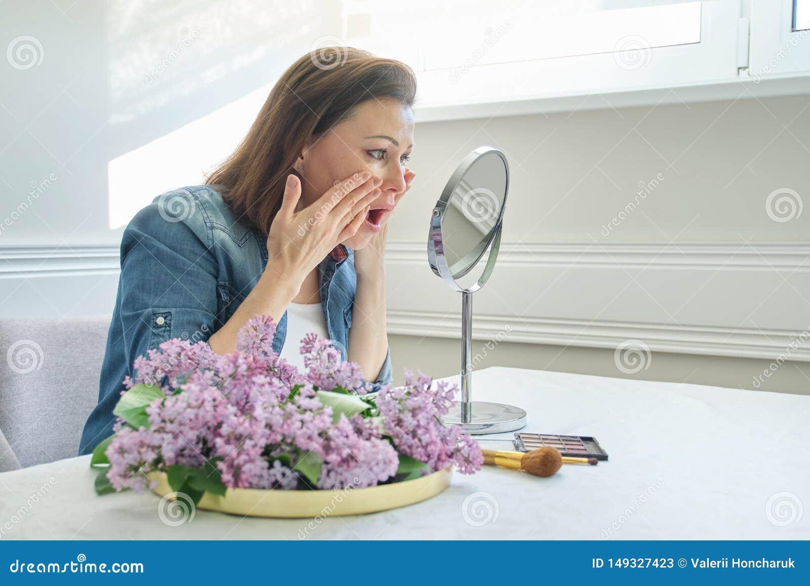 Ritratto della donna matura con lo specchio di trucco che massaggia il suoi fronte e collo, bei 40 anni femminili