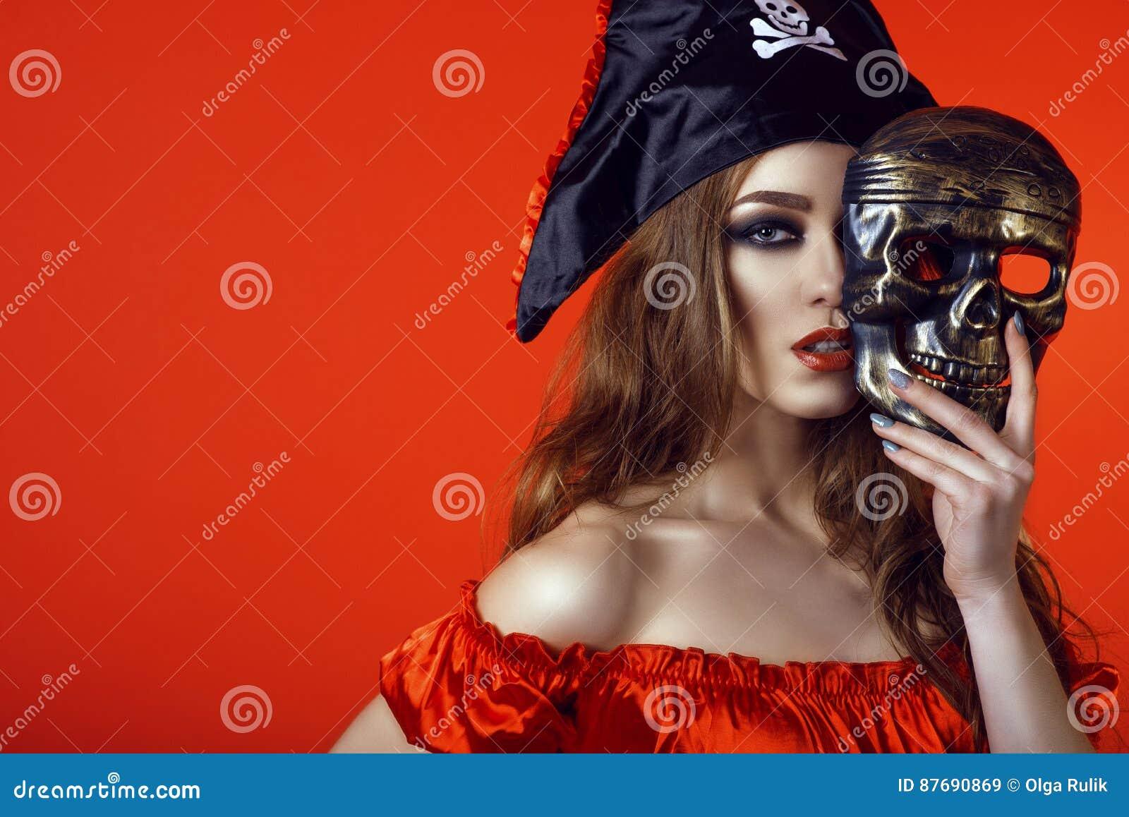 Ritratto della donna sexy splendida con trucco provocatorio in costume del pirata che nasconde la metà del suo fronte dietro la m