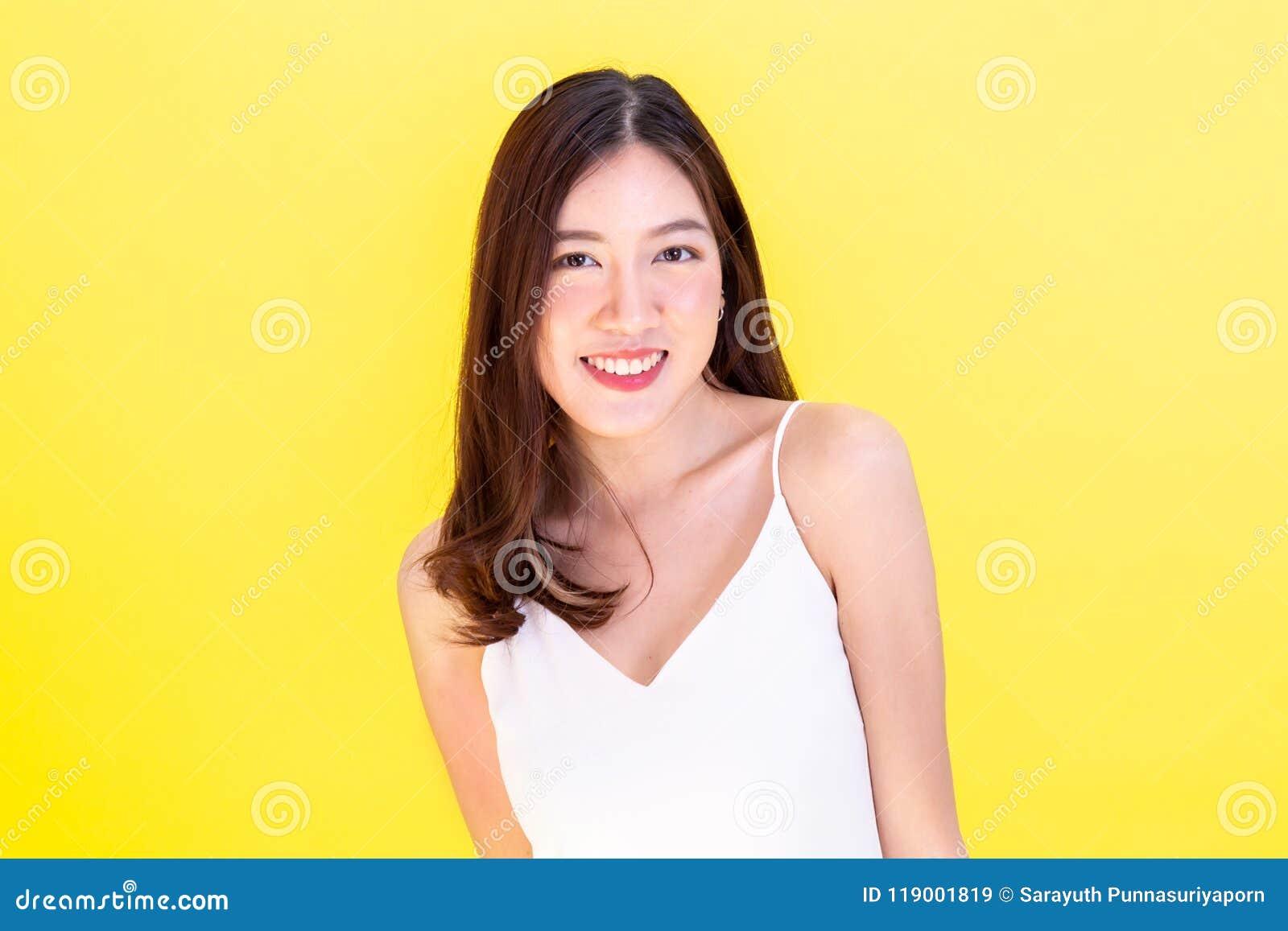 Ritratto della donna sorridente asiatica attraente che mostra espressione sveglia
