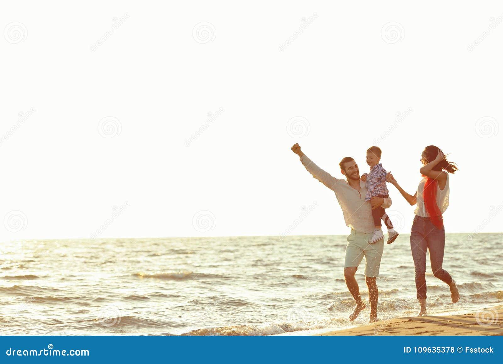 Ritratto della famiglia felice e del bambino che godono del tramonto nello svago di estate