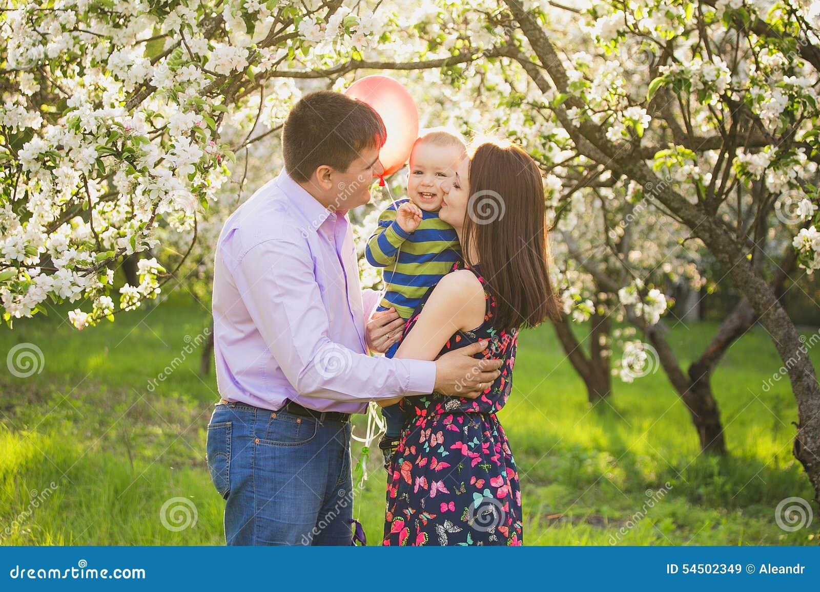 Ritratto della famiglia felice padre, madre, abbracciare del bambino e bacio