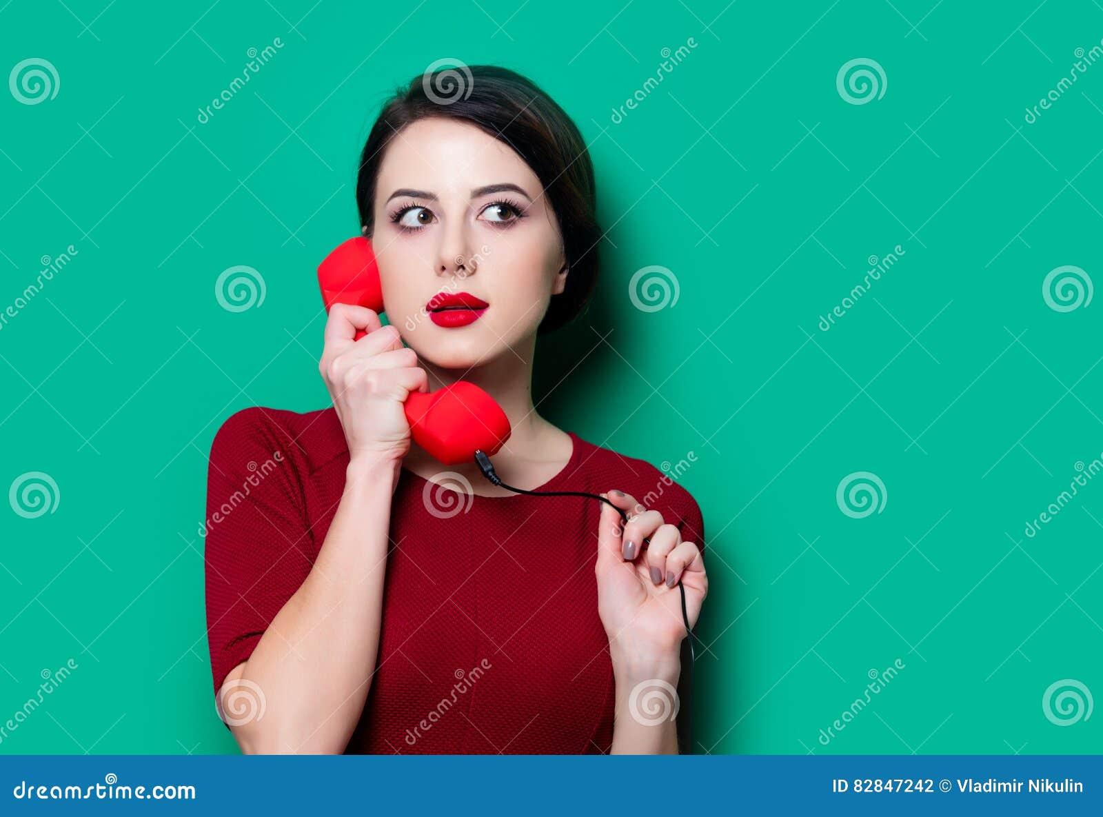 Ritratto della giovane donna con il microtelefono rosso