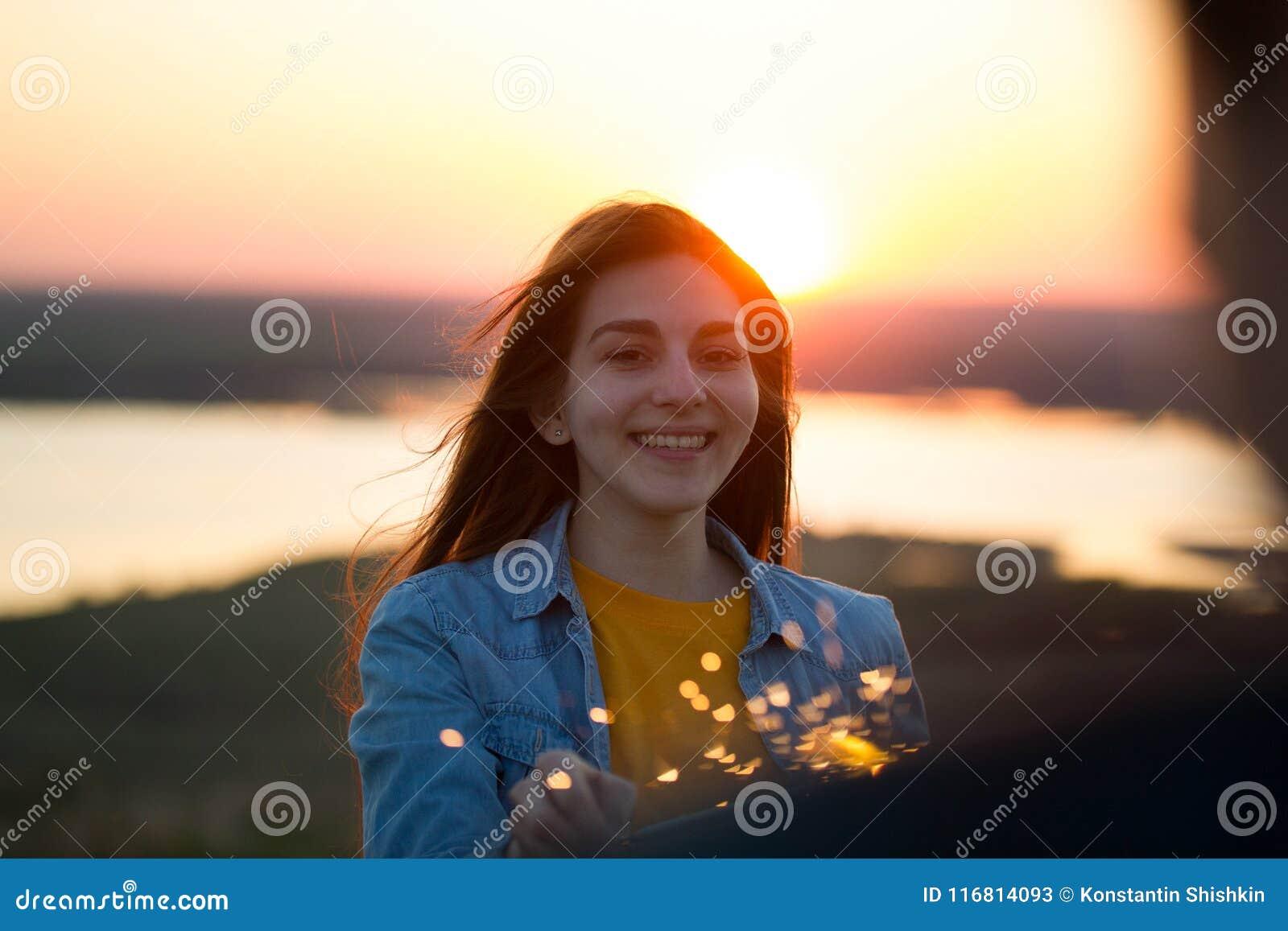 Ritratto della giovane donna felice con la stella filante a disposizione nella sera di estate