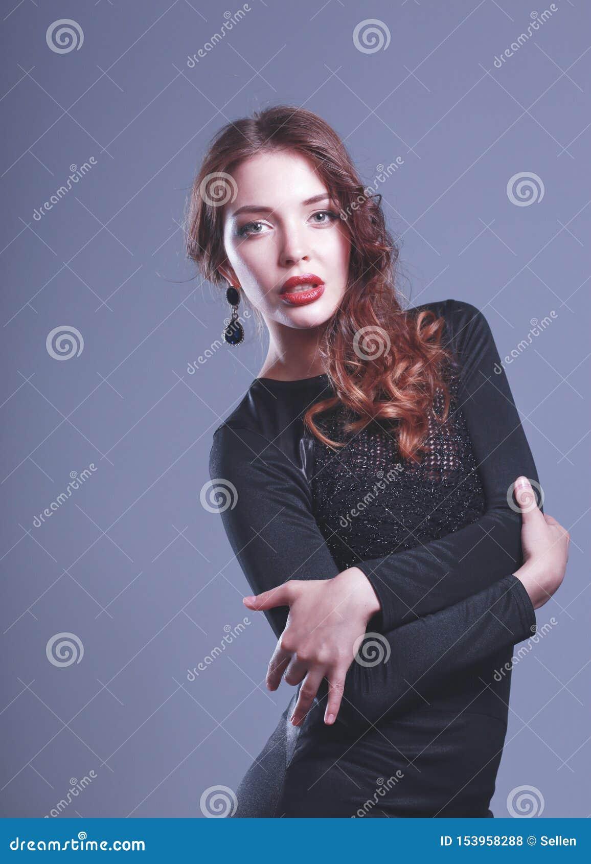 Ritratto della giovane donna felice in vestito nero su fondo grigio