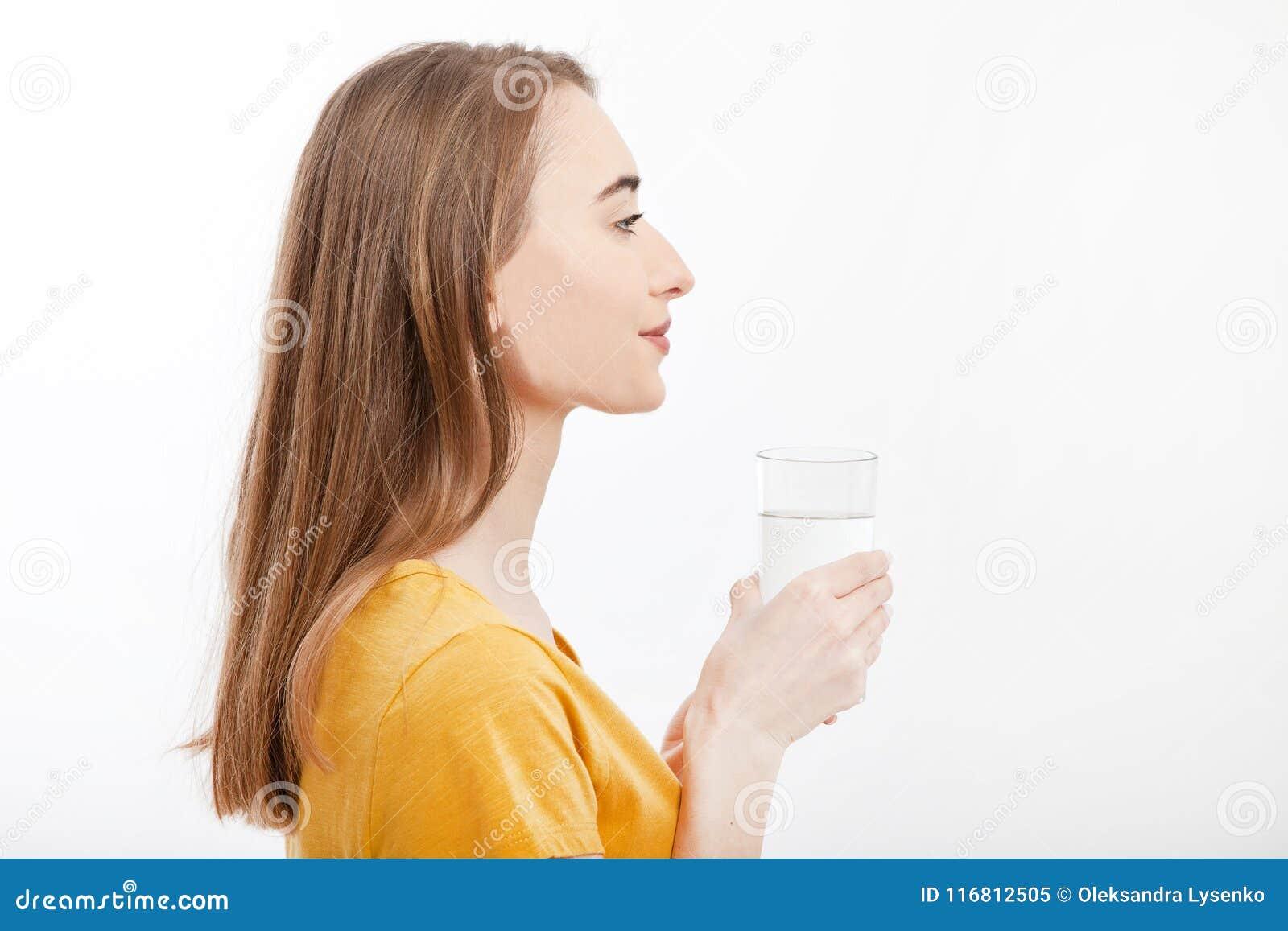 Ritratto della giovane donna sorridente che sta nel profilo e che tiene un bicchiere d acqua Priorità bassa bianca Derisione su