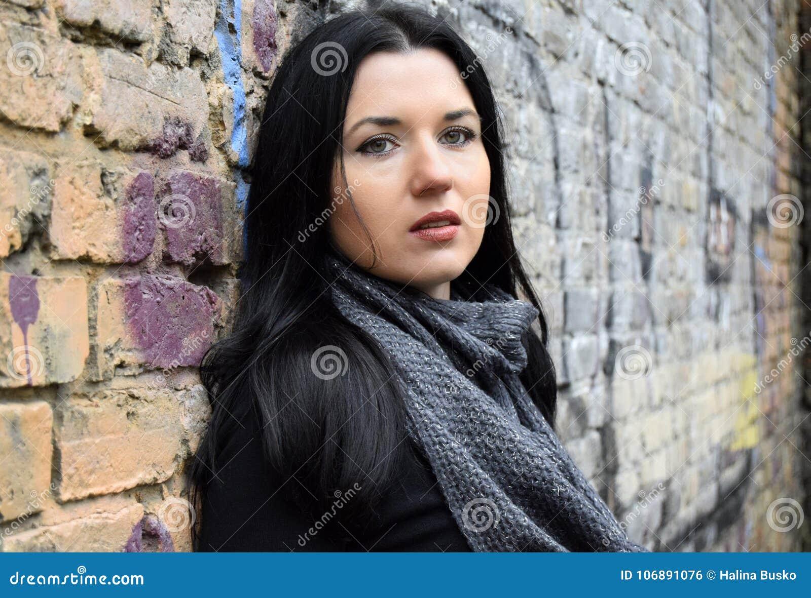 Ritratto della giovane donna della st castana i precedenti di vecchio muro di mattoni ancora