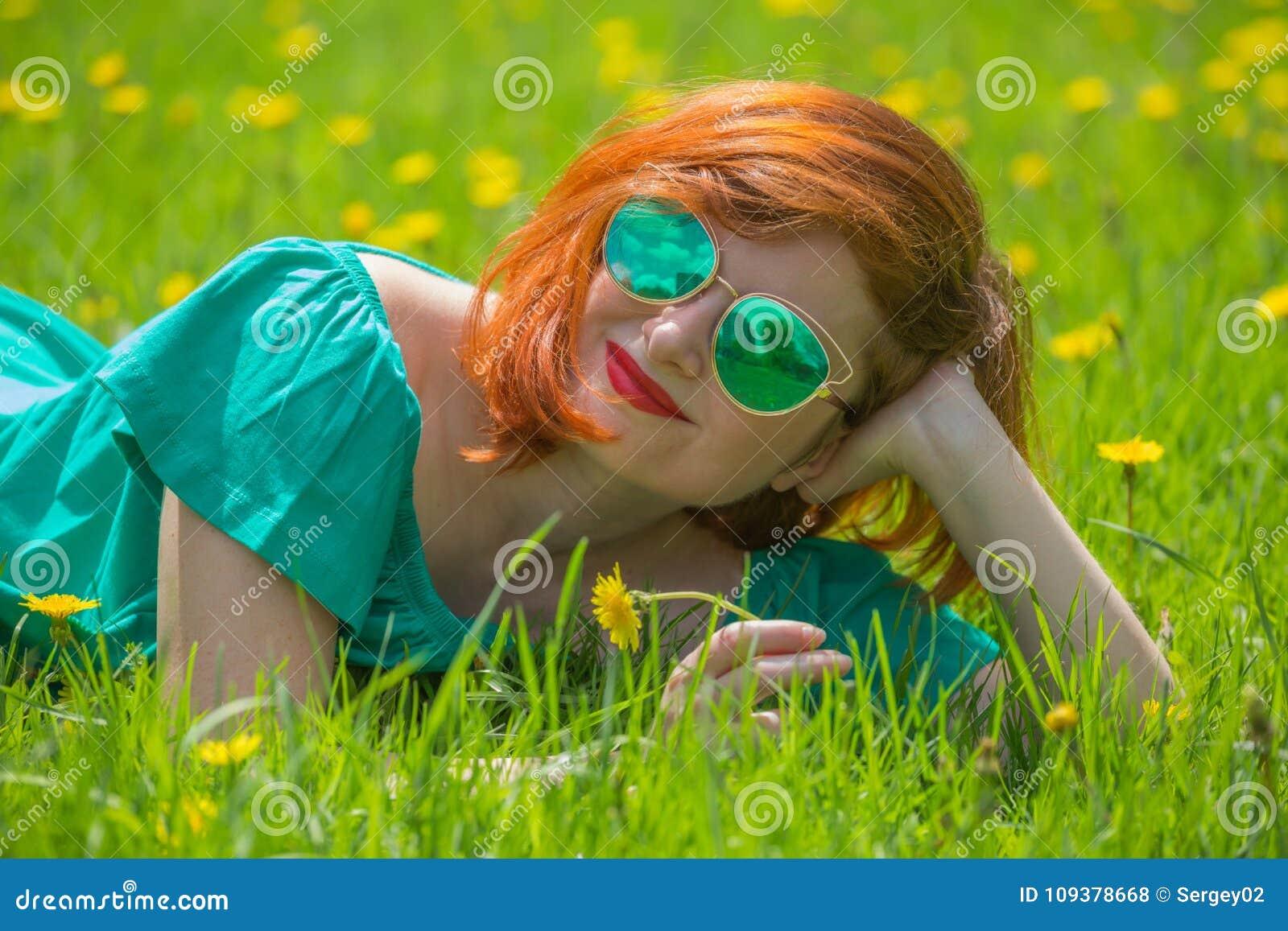 Ritratto della giovane donna della testarossa che si rilassa nel parco di primavera