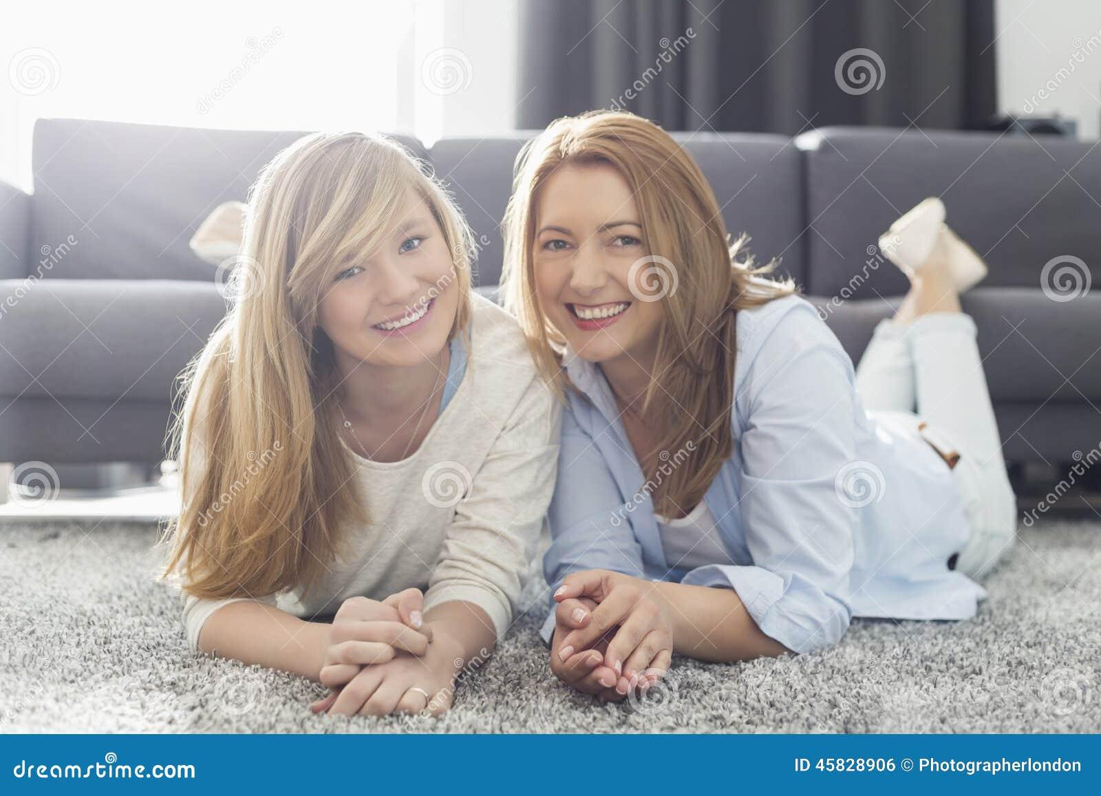 Ritratto della madre e della figlia sorridenti che si trovano sul tappeto