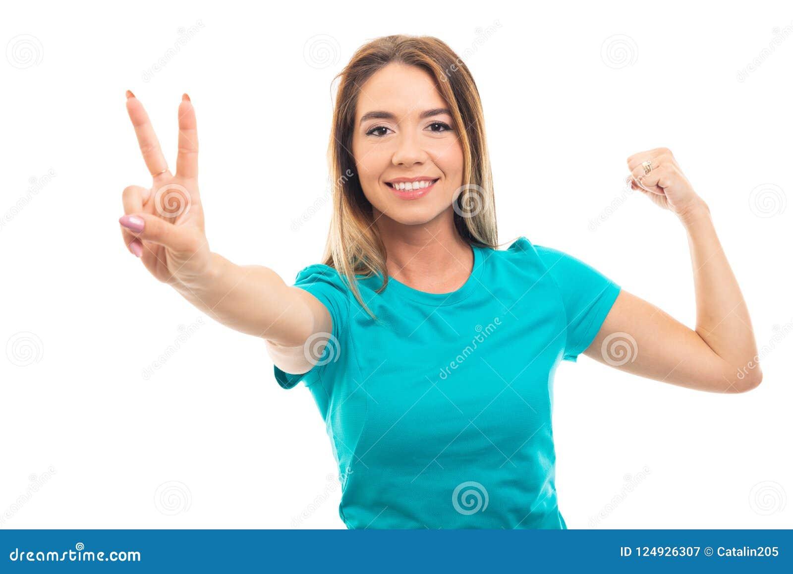 Ritratto della maglietta d uso della giovane ragazza graziosa che mostra il GE di vittoria