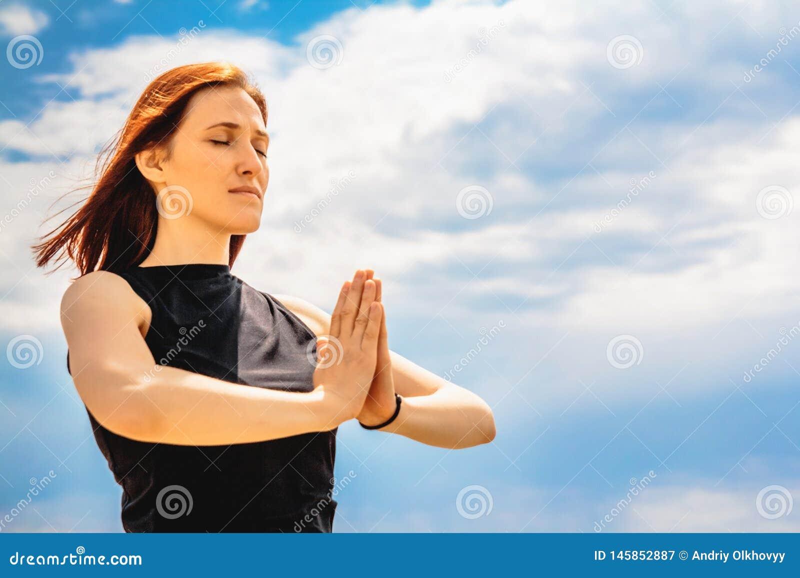 Ritratto della posizione di rilassamento di yoga della donna attraente di forma fisica contro il fondo del cielo