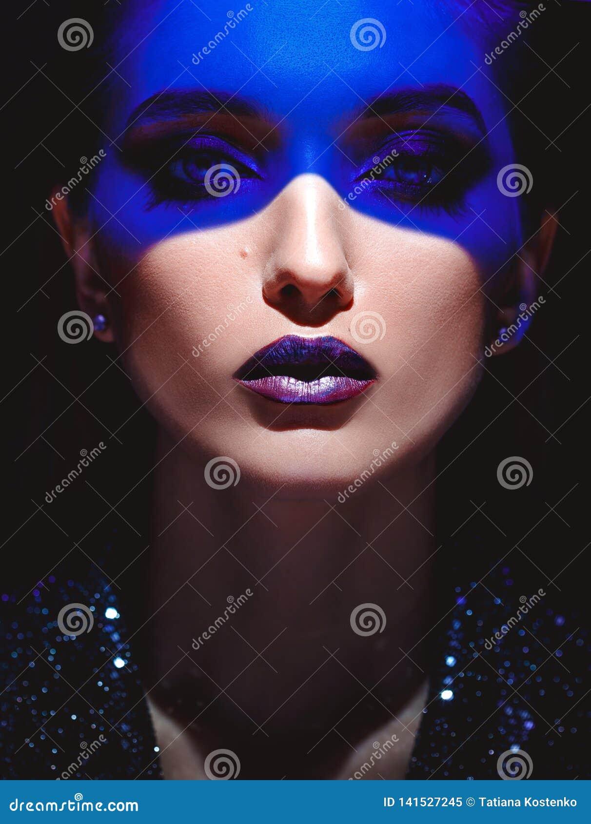 Ritratto della ragazza di modo con trucco alla moda e della luce al neon blu sul suo fronte sui precedenti neri nello studio