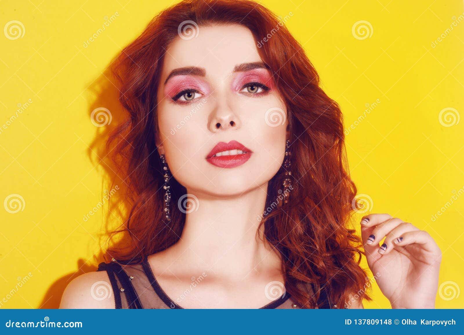 Ritratto della ragazza di modo sulla posa gialla del fondo La ragazza castana graziosa con lungamente cerly capelli ed il rosa co