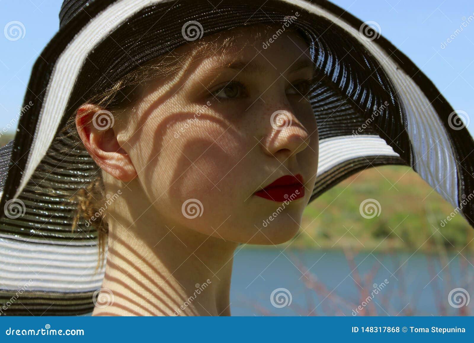 Ritratto della ragazza graziosa che indossa un black hat, all aperto, fine su la gente, concetto di viaggio