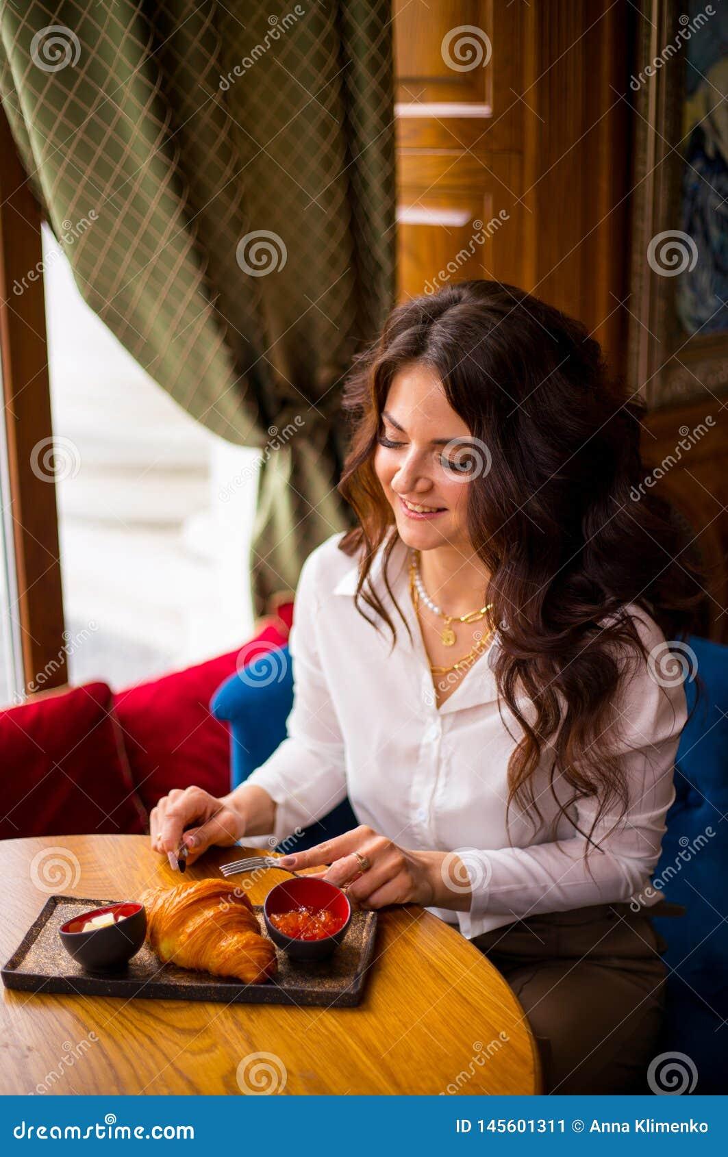 Ritratto della ragazza incantante in caffetteria moderna alla prima colazione, prima colazione piacevole della donna in caffè man