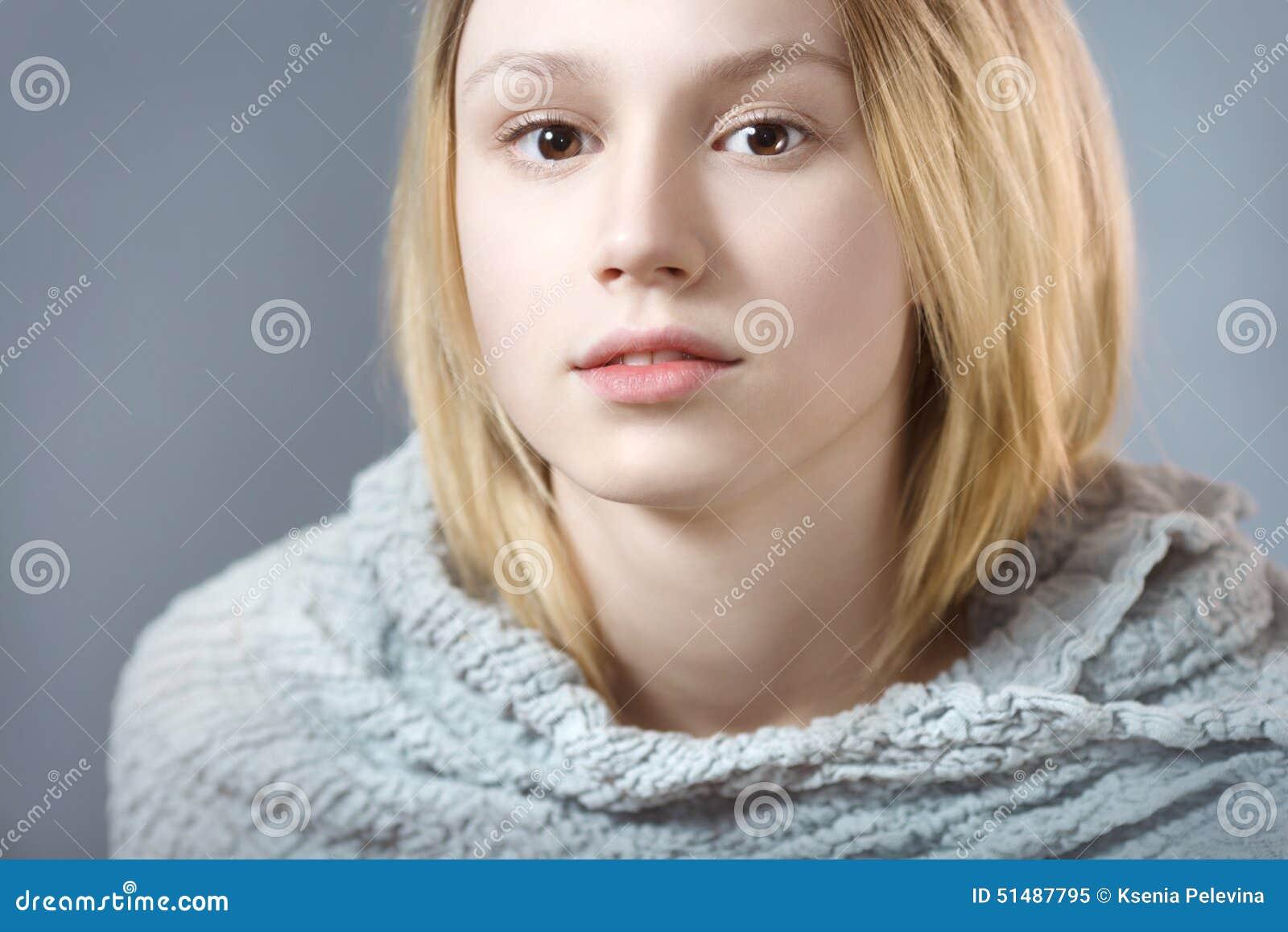 Ritratto della ragazza pensierosa in primo piano grigio di colori pastelli