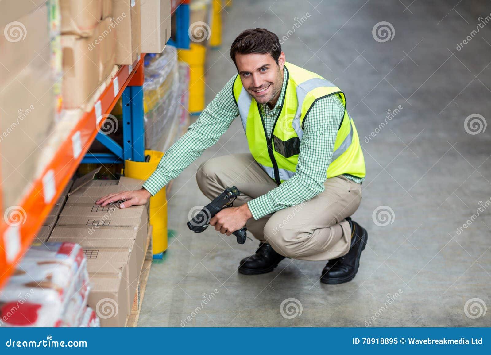 Ritratto della scatola sorridente di esame del lavoratore del magazzino
