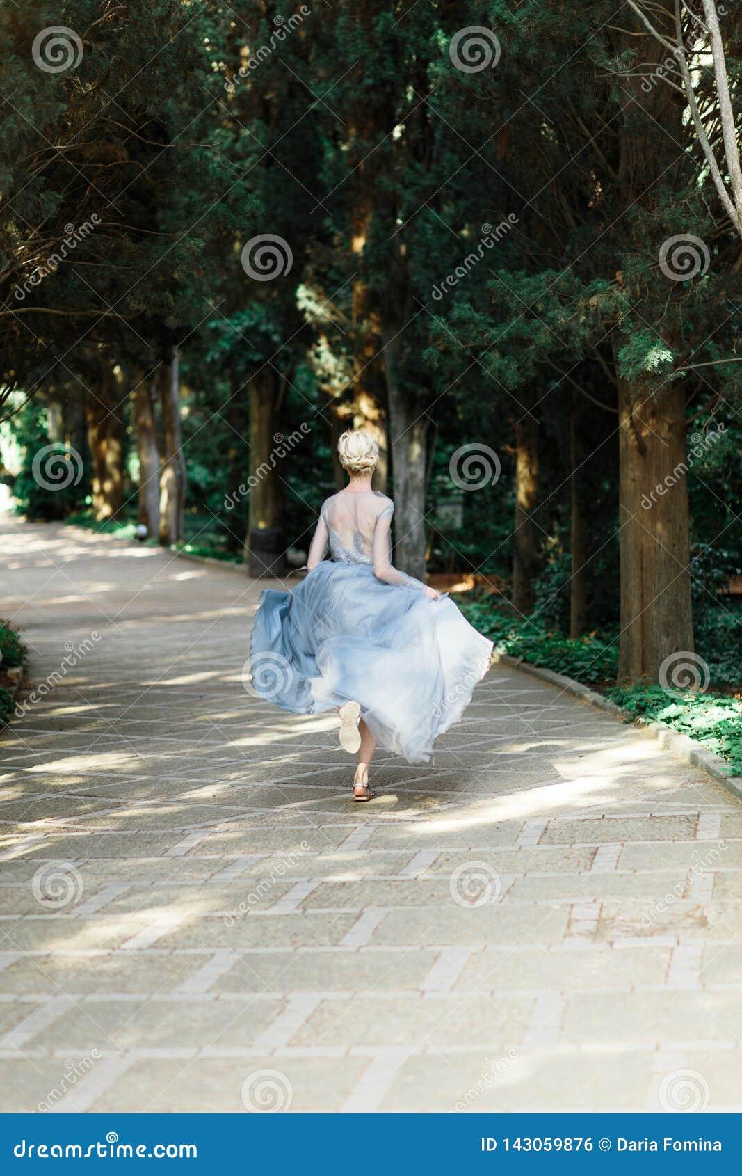 Ritratto della sposa di stordimento in bello vestito da sposa su sfondo naturale