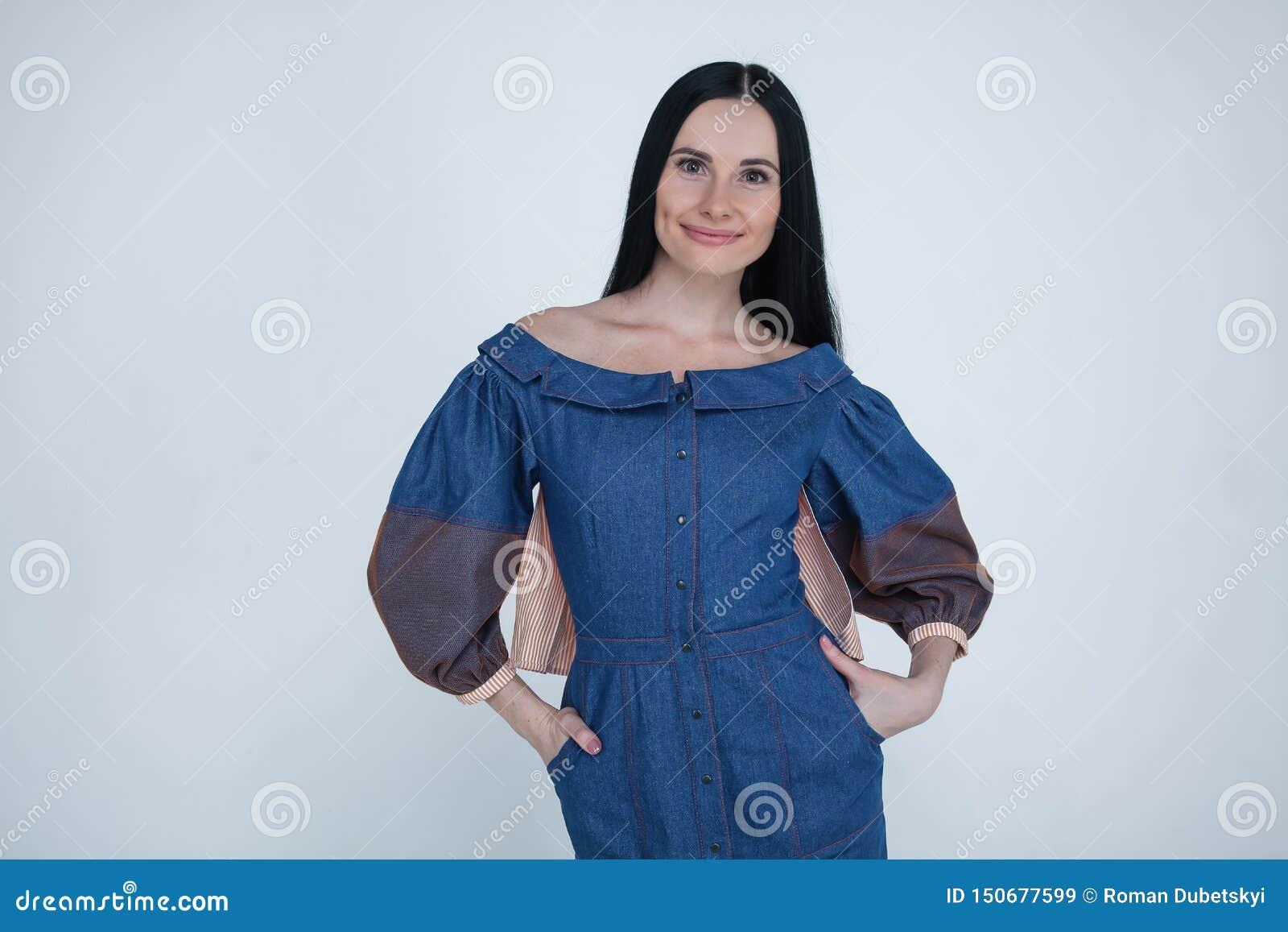 Ritratto della vita-su di bella donna castana che indica le dita a sinistra d angolo, spazio per il vostro testo o logo Vestito d