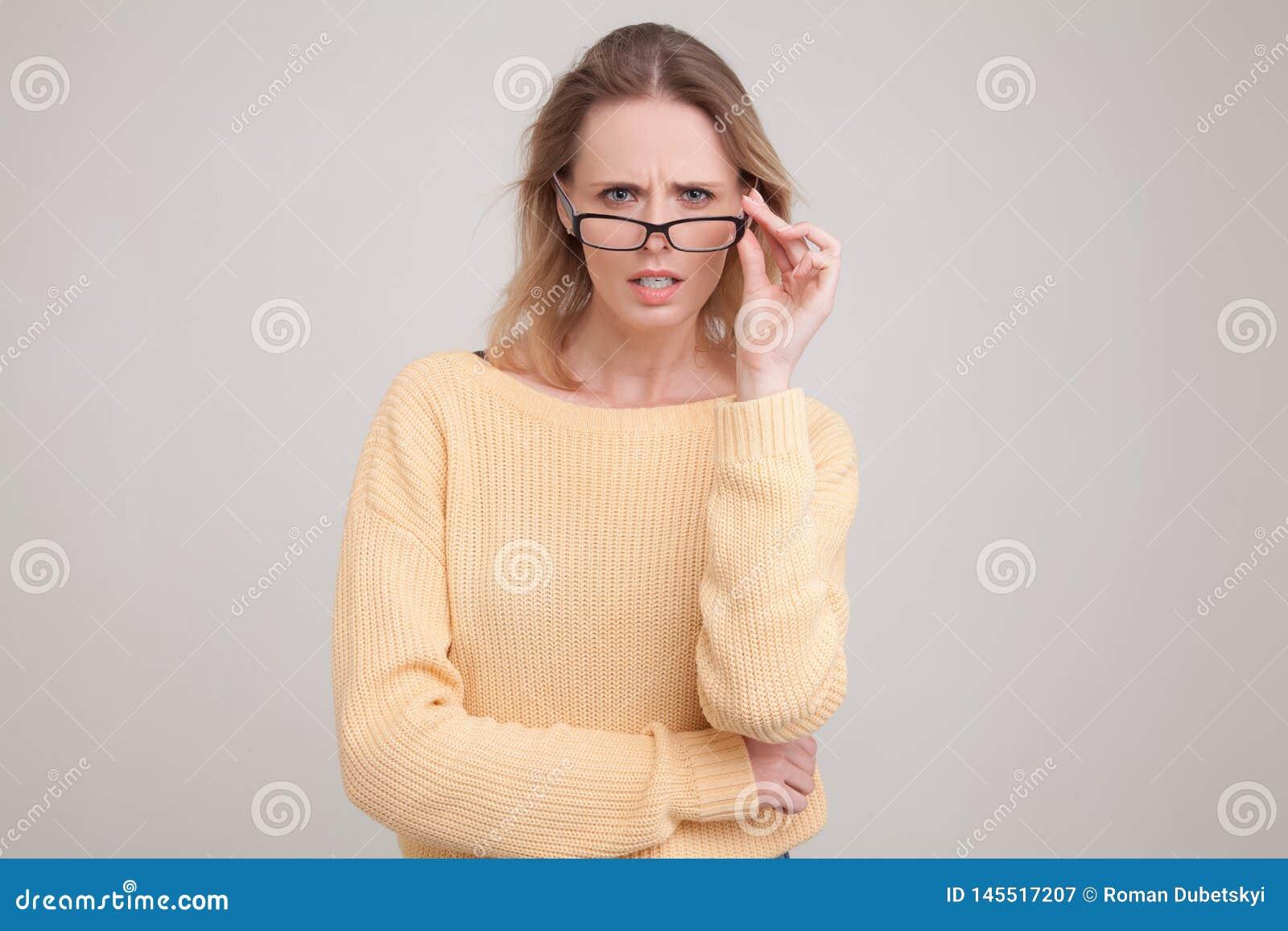 Ritratto della vita-su di giovane donna bionda con emozione sorpresa sul suo fronte esaminando la macchina fotografica, nota qual