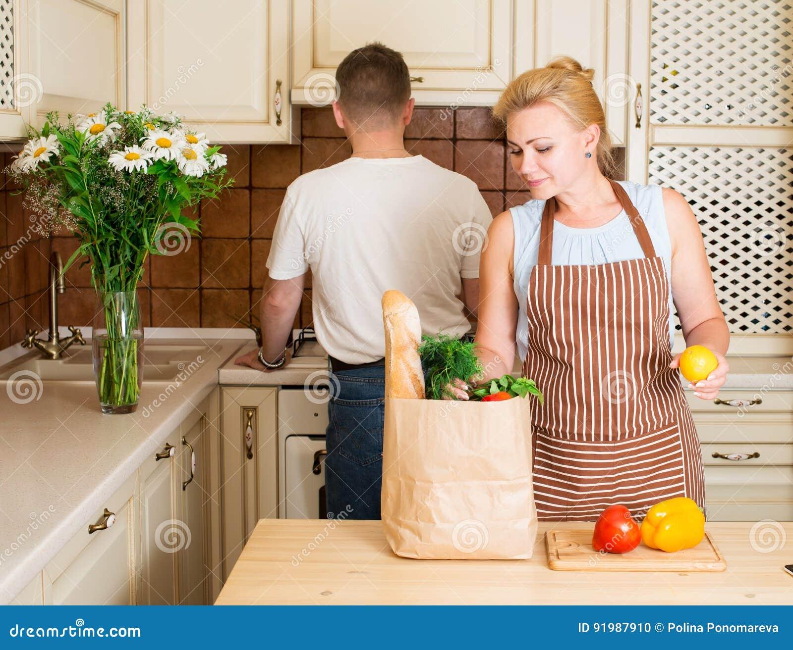 Ritratto delle coppie felici con il sacco di carta della drogheria con le verdure