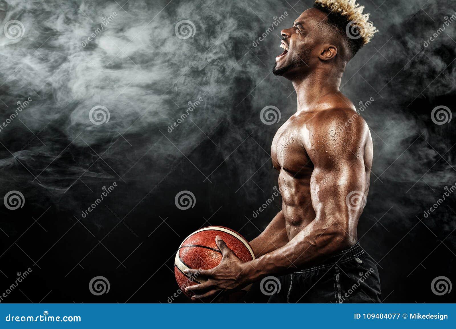 Ritratto dello sportivo afroamericano, giocatore di pallacanestro con una palla sopra fondo nero Giovane adatto in abiti sportivi