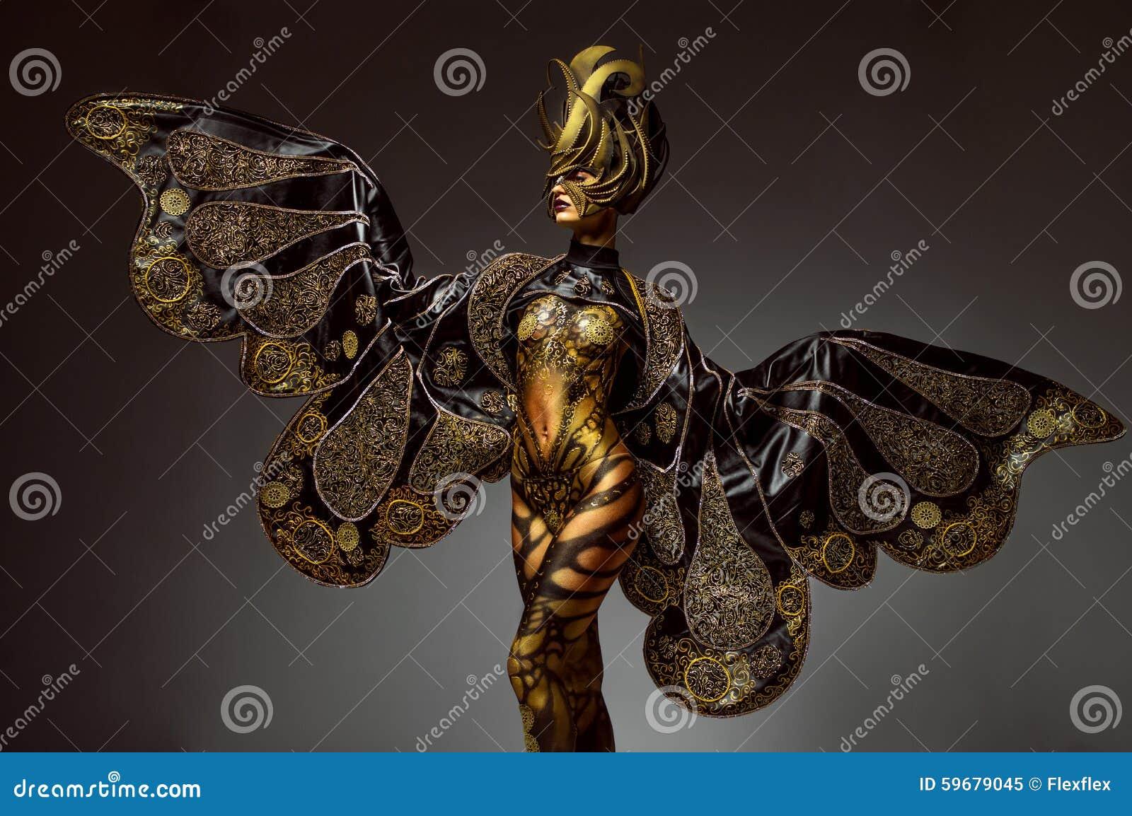 Ritratto dello studio di bello modello con body art dorato della farfalla di fantasia