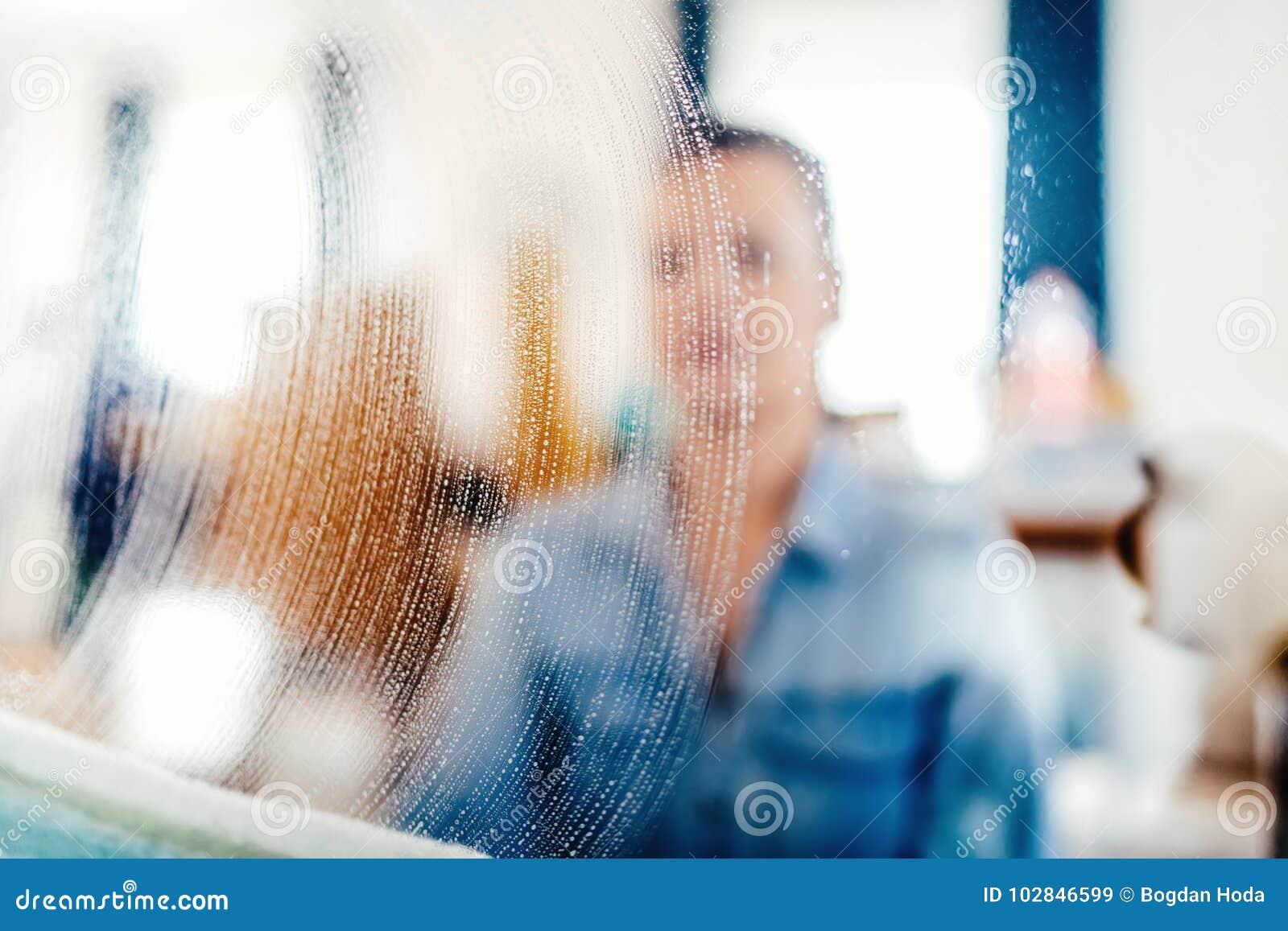 Ritratto, dettagli fuori vaghi di pulizia di finestra Detersivo e panno del sapone sul vetro di finestra