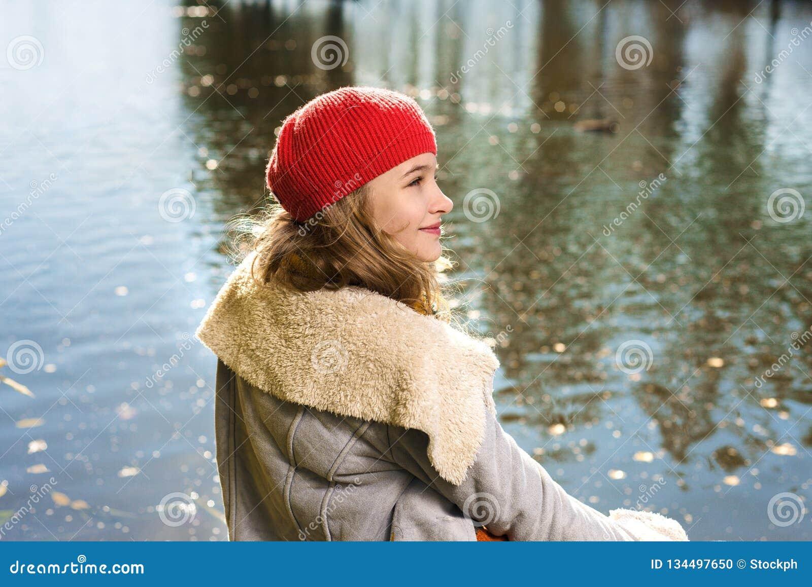 Ritratto di autunno di giovane ragazza graziosa in cappello rosso