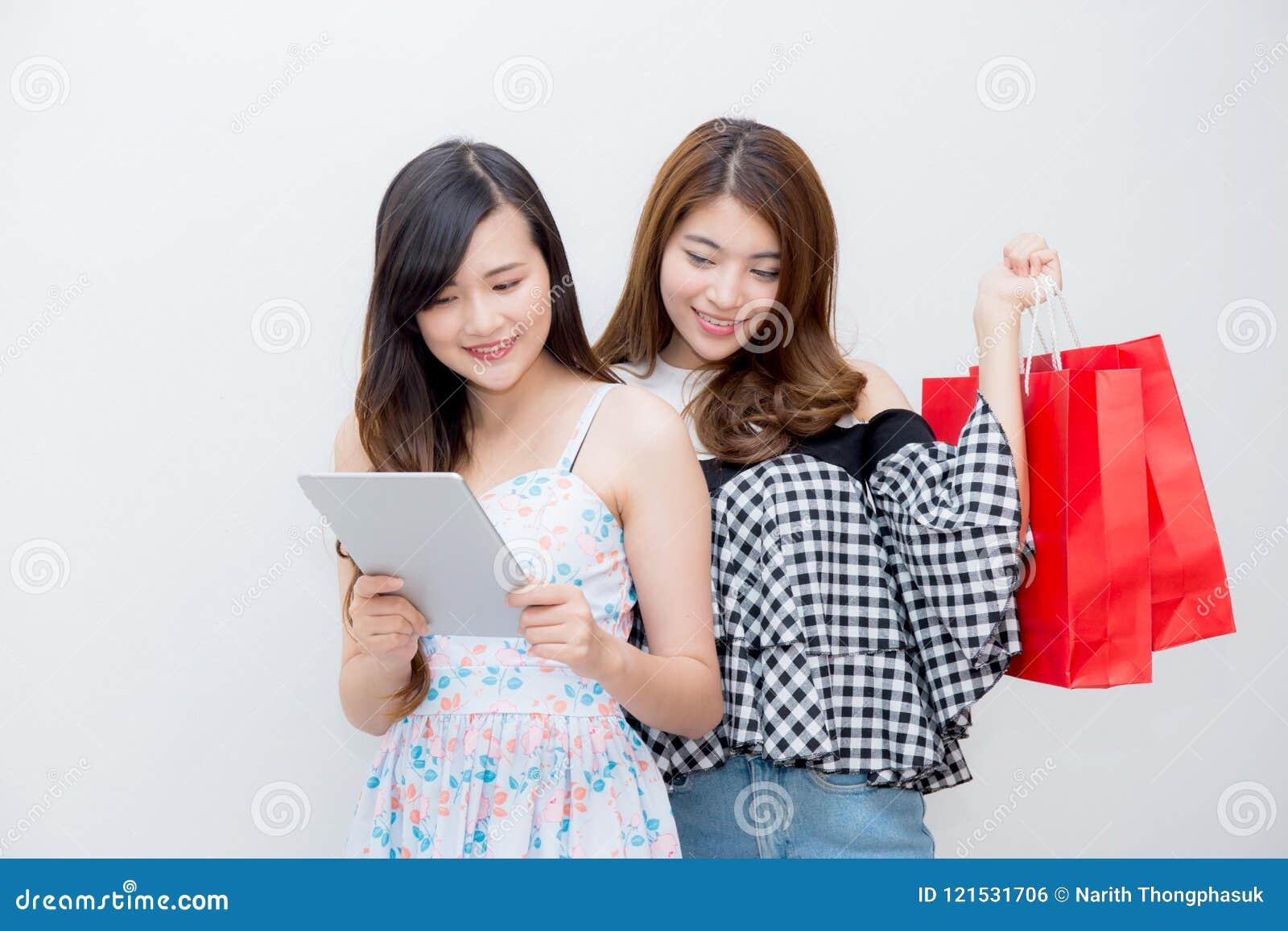 Ritratto di bei sacchetto della spesa della tenuta della donna della gente dei giovani due e computer asiatici della compressa