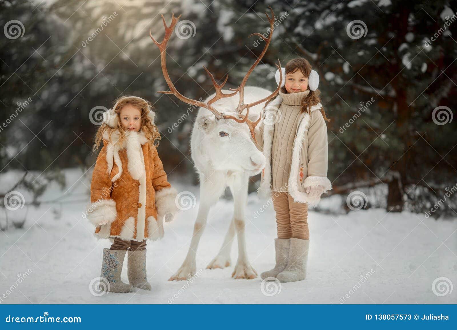 Ritratto di bella bambina in pelliccia alla foresta di inverno