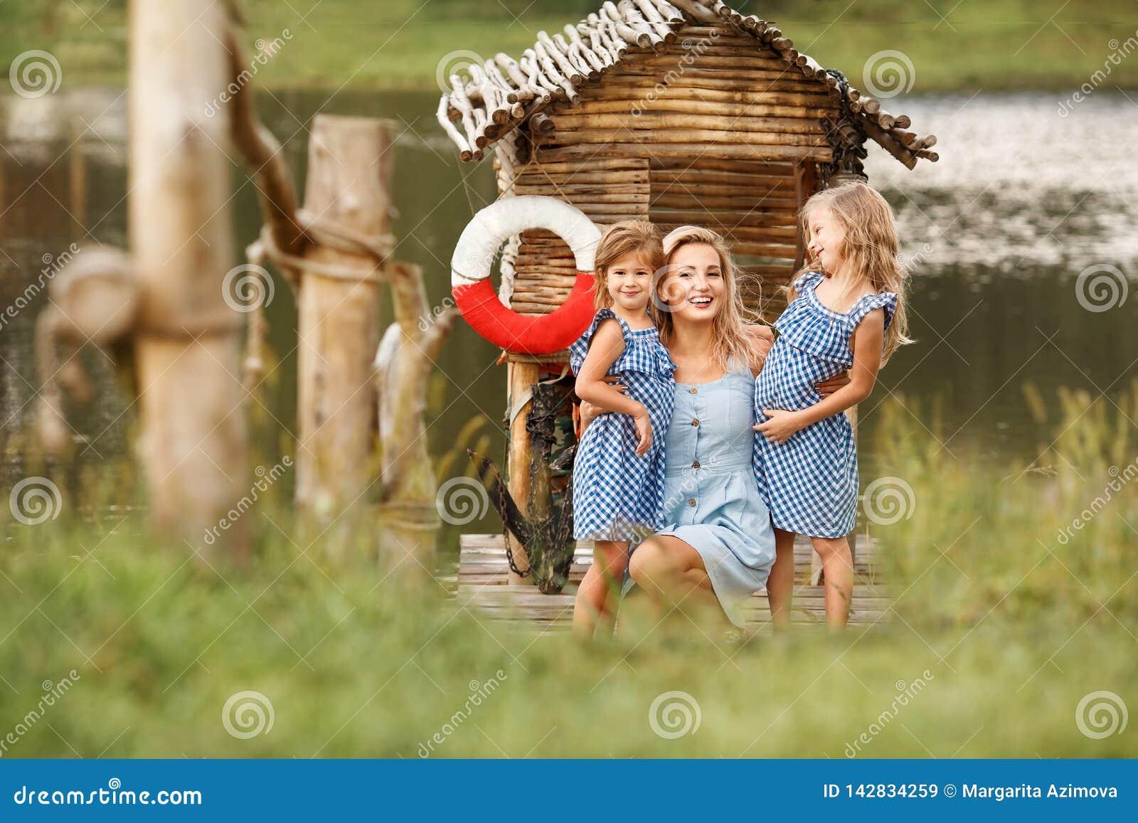 Ritratto di bella donna bionda che cammina con la figlia due vicino al lago al tramonto