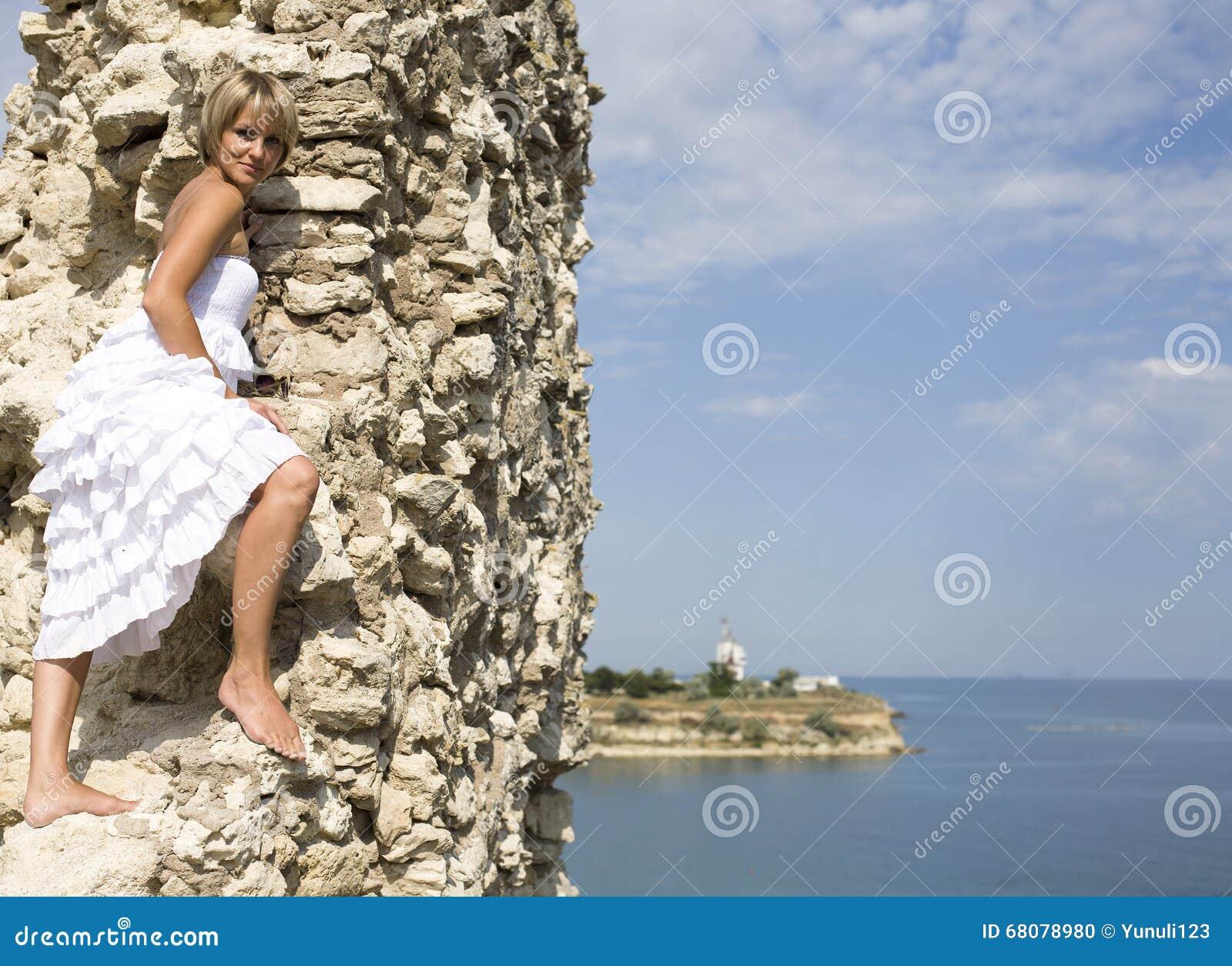 1ad51c5bffbf Ritratto di bella donna bionda in vestito bianco che sta sul vento con la  sciarpa vicino al mare fra erba gialla