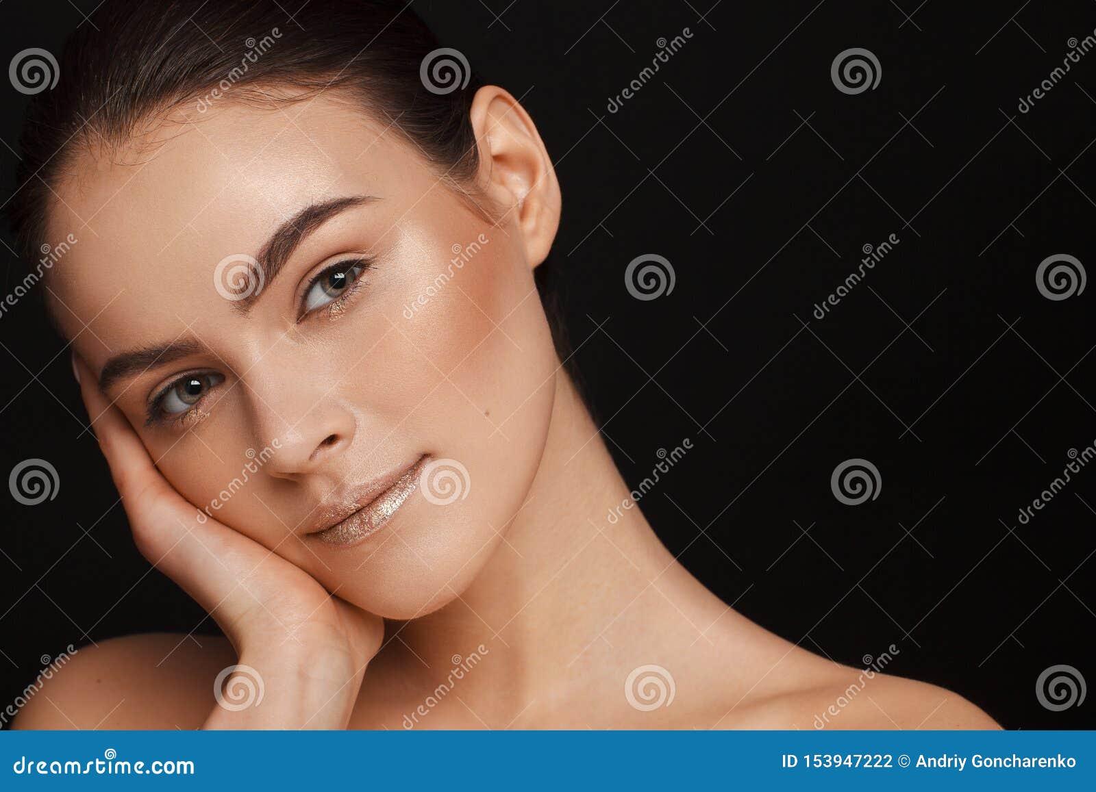 Ritratto di bella donna con capelli raccolti e delle spalle nude su un fondo nero