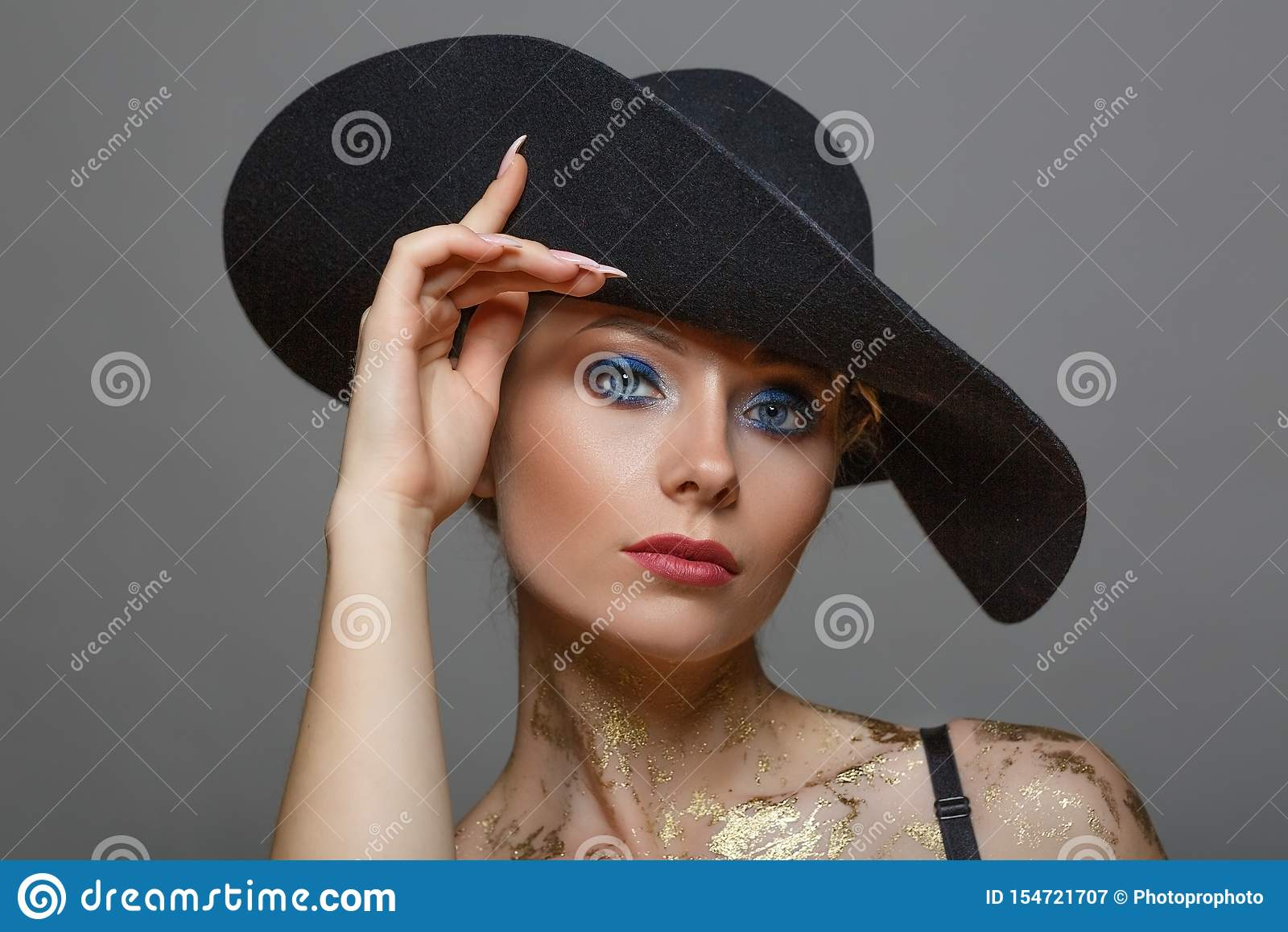 Ritratto di bella donna dentro con trucco in black hat su fondo bianco, isolato
